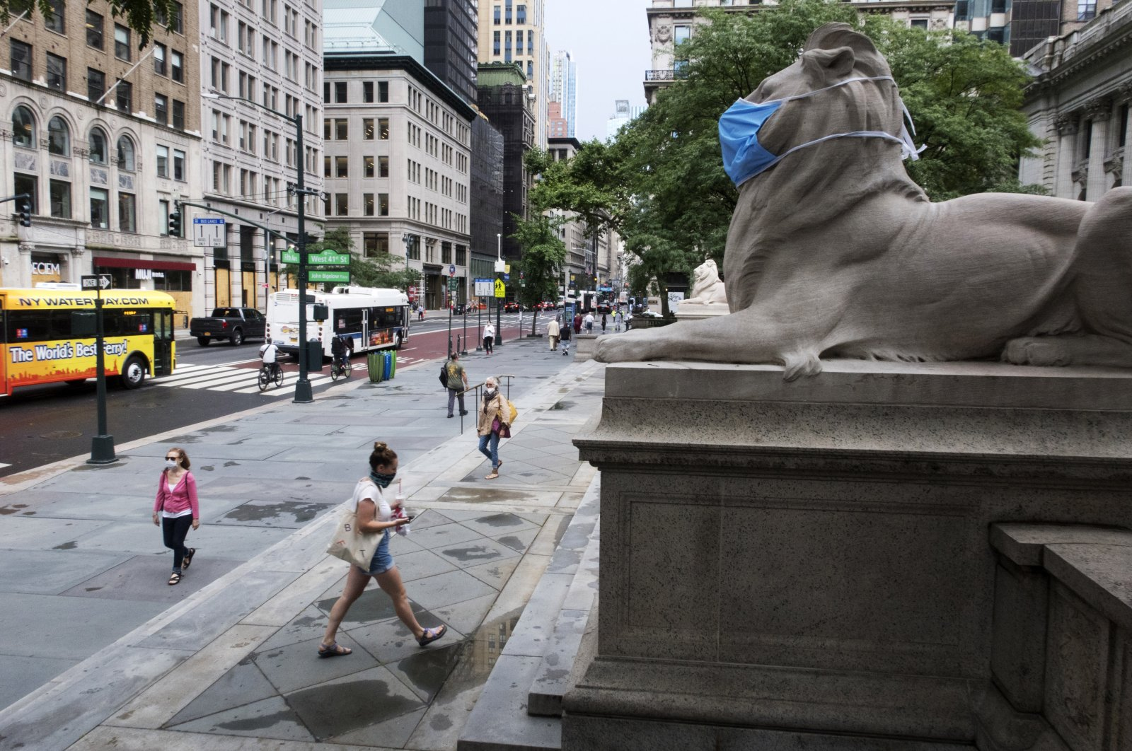 A face mask covers the mouth and nose of one of the iconic lion statues in front of the New York Public Library's main branch, New York City, July 1, 2020. (AP Photo)