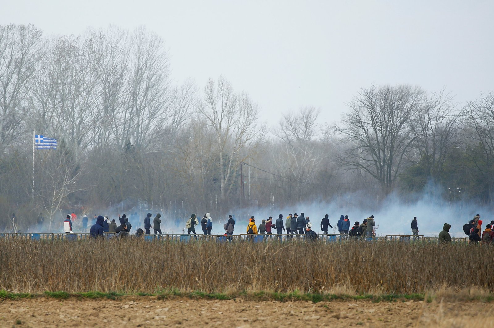 Tear gas thrown by police floats in the air among migrants near Turkey's Pazarkule border crossing with Greece's Kastanies, near Edirne, Turkey, March 4, 2020. (Reuters Photo)