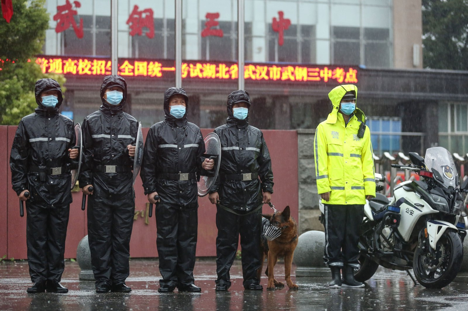 Police officers stand guard outside a school as students arrive for the National College Entrance Examination (NCEE), known as Gaokao, in Wuhan in China's central Hubei province, July 7, 2020. (AFP Photo)