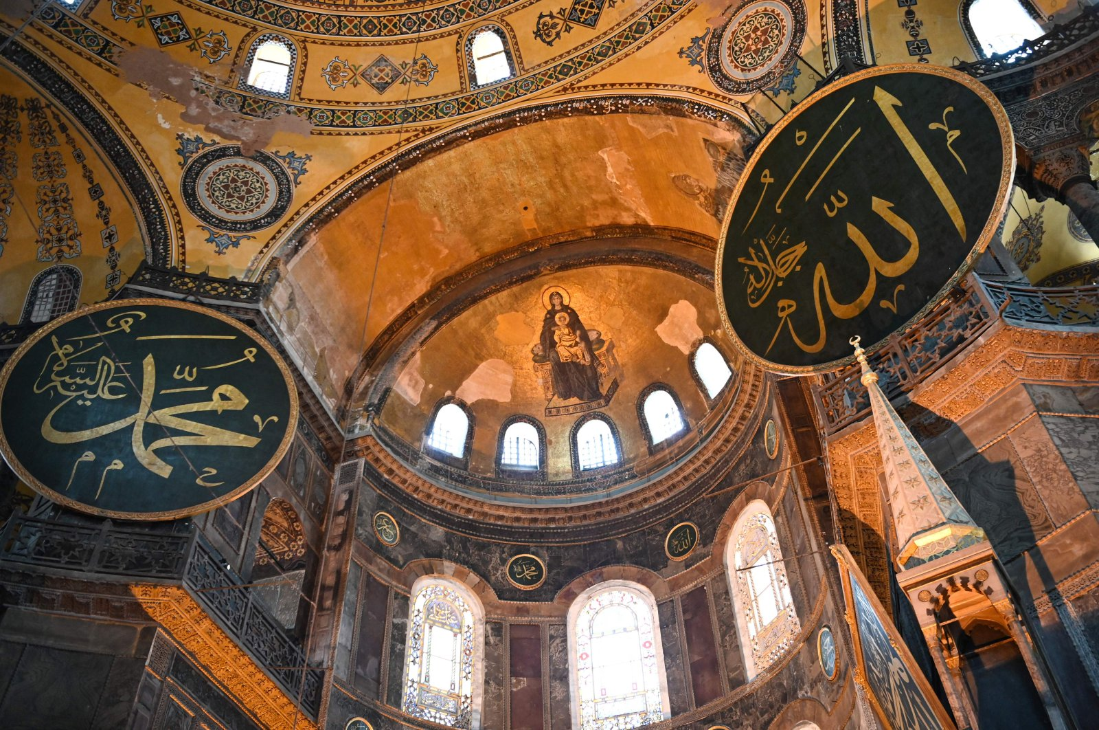 A fresco of the Virgin Mary and child and a calligraphic Roundels with Arabic letters bearing the name of Allah and other Muslim prophets hanging on the dome of the Hagia Sophia Museum in Istanbul, July 2, 2020. (AFP Photo)