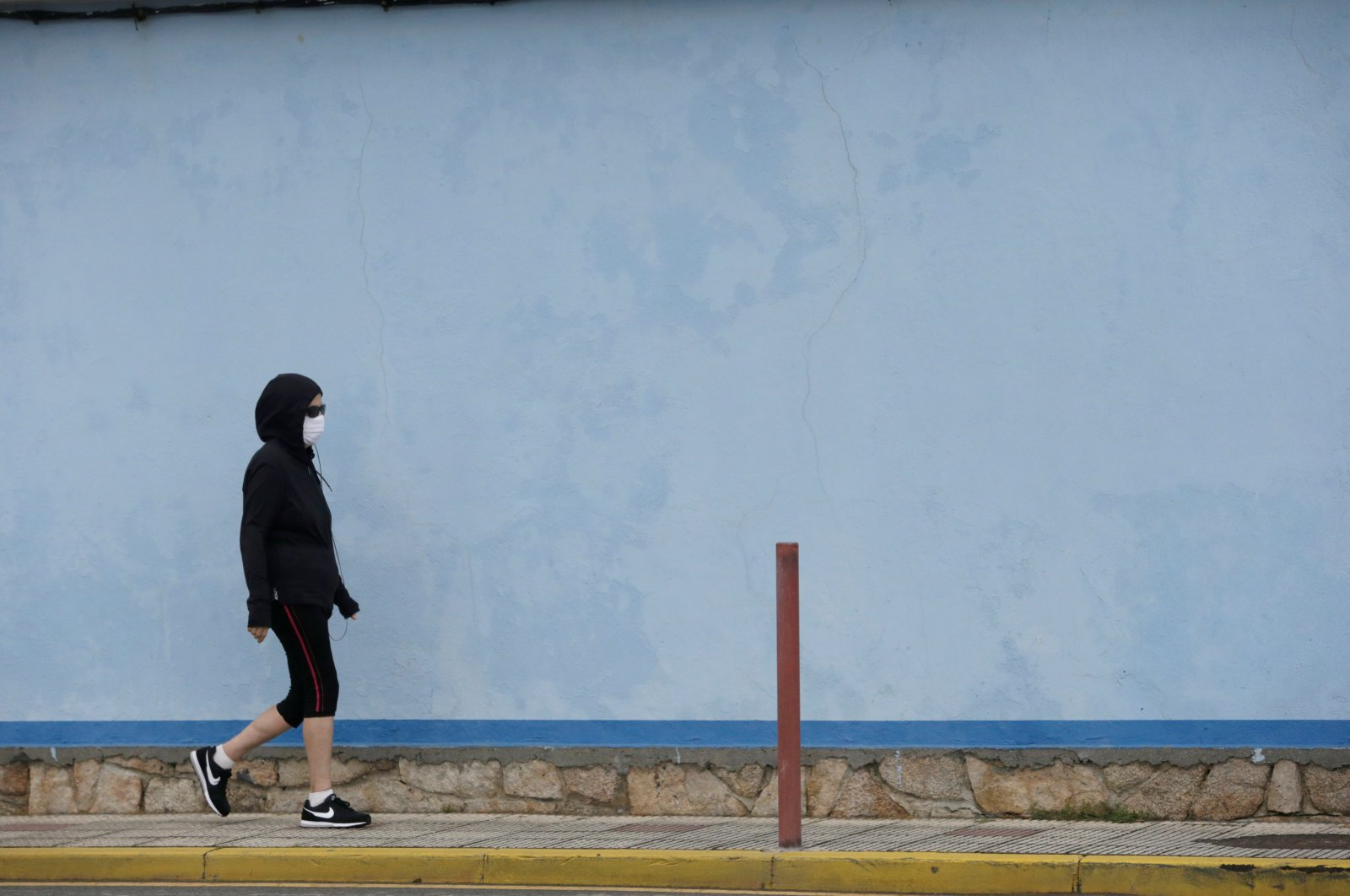 A woman wearing a protective face mask walks during the lockdown, Burela, Spain, July 6, 2020. (Reuters Photo)