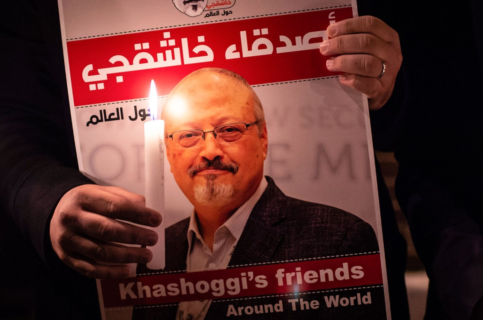 A demonstrator holds a poster picturing Saudi journalist Jamal Khashoggi and a lighted candle during a gathering outside Saudi Arabia's consulate in Istanbul, Turkey, Oct. 25, 2018. (AFP Photo)