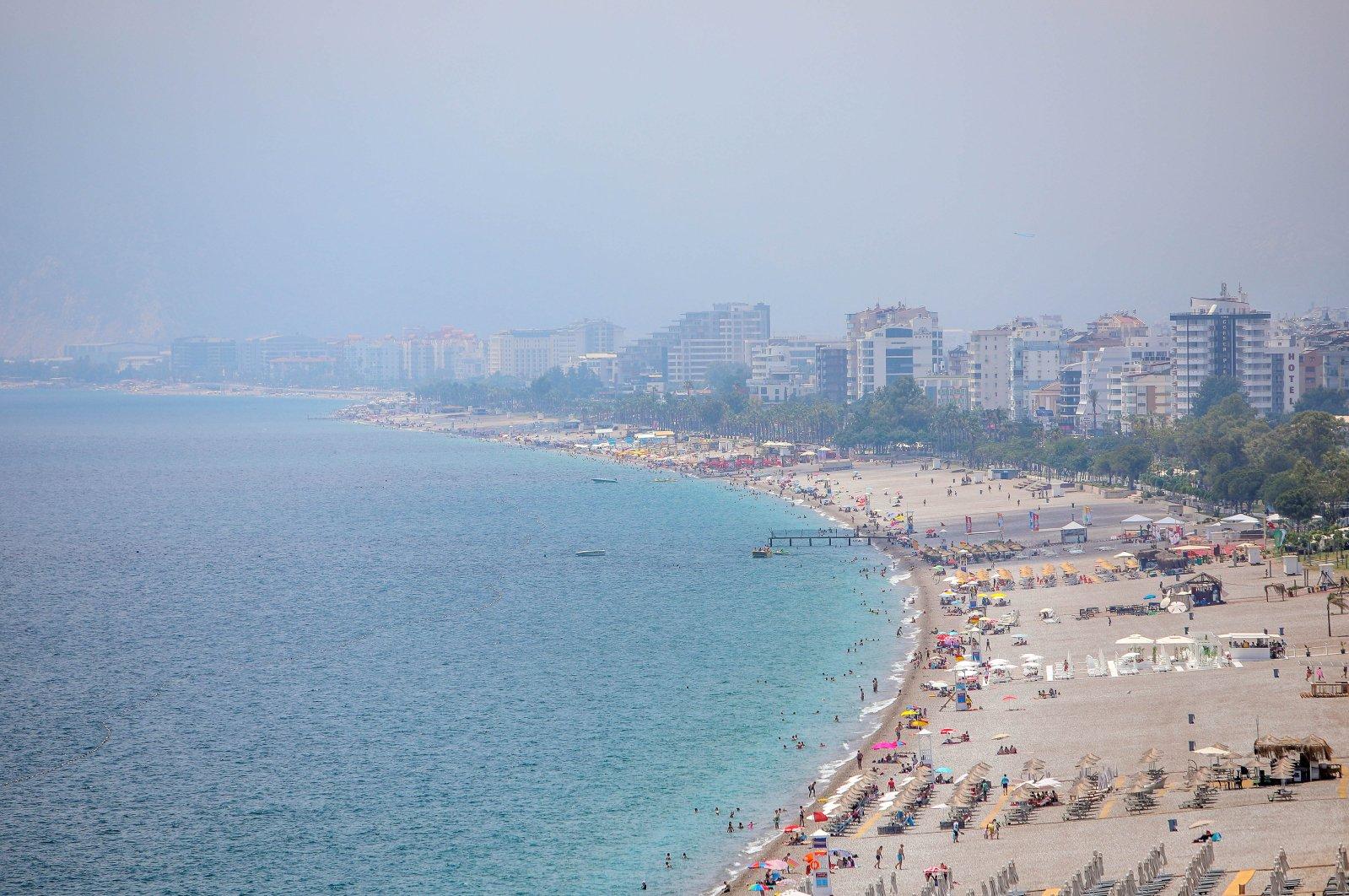 People enjoy the sun at Konyaaltı Beach in Antalya, Turkey, July 6, 2020. (DHA Photo)