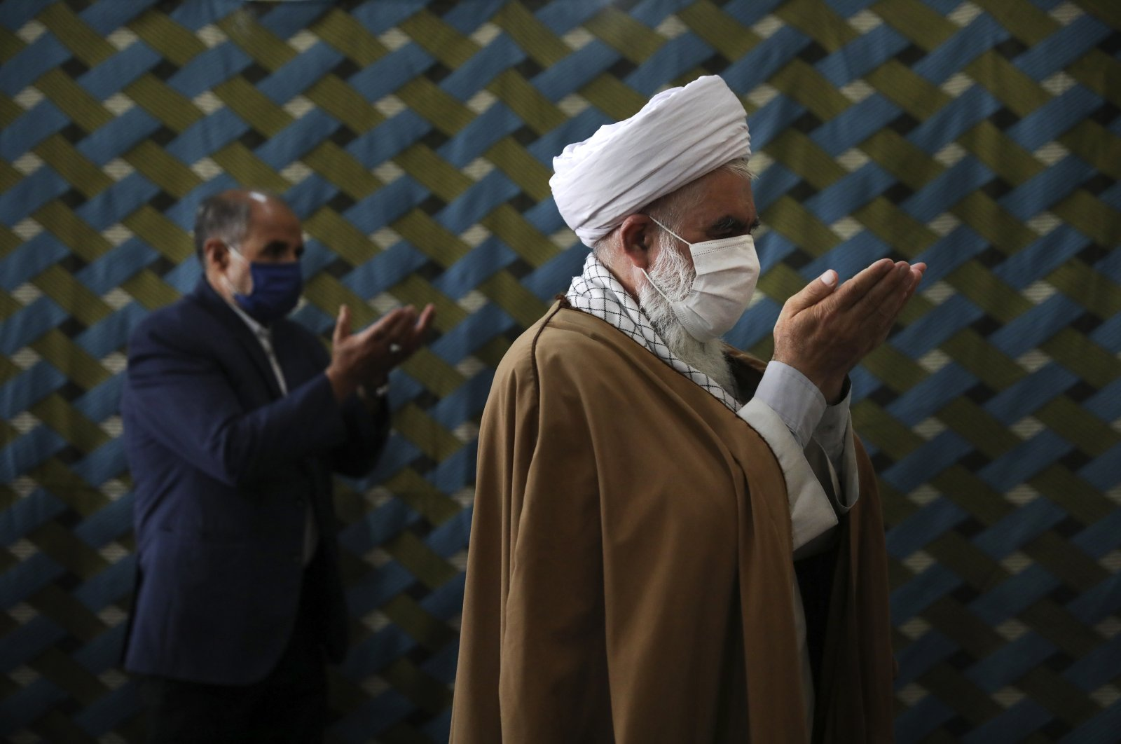 A cleric wearing a protective face mask to help prevent the spread of the coronavirus, leads the noon prayer at a mosque in the the city of Zanjan, some 330 kilometers west of capital Tehran, Iran, July 5, 2020. (AP Photo)