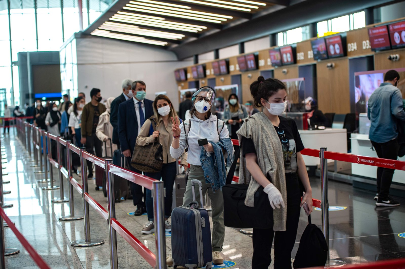 Travelers at the Istanbul Airport wearing protective face masks queue as an employee serves a passenger, Istanbul, Turkey, June 1, 2020. (AFP Photo)