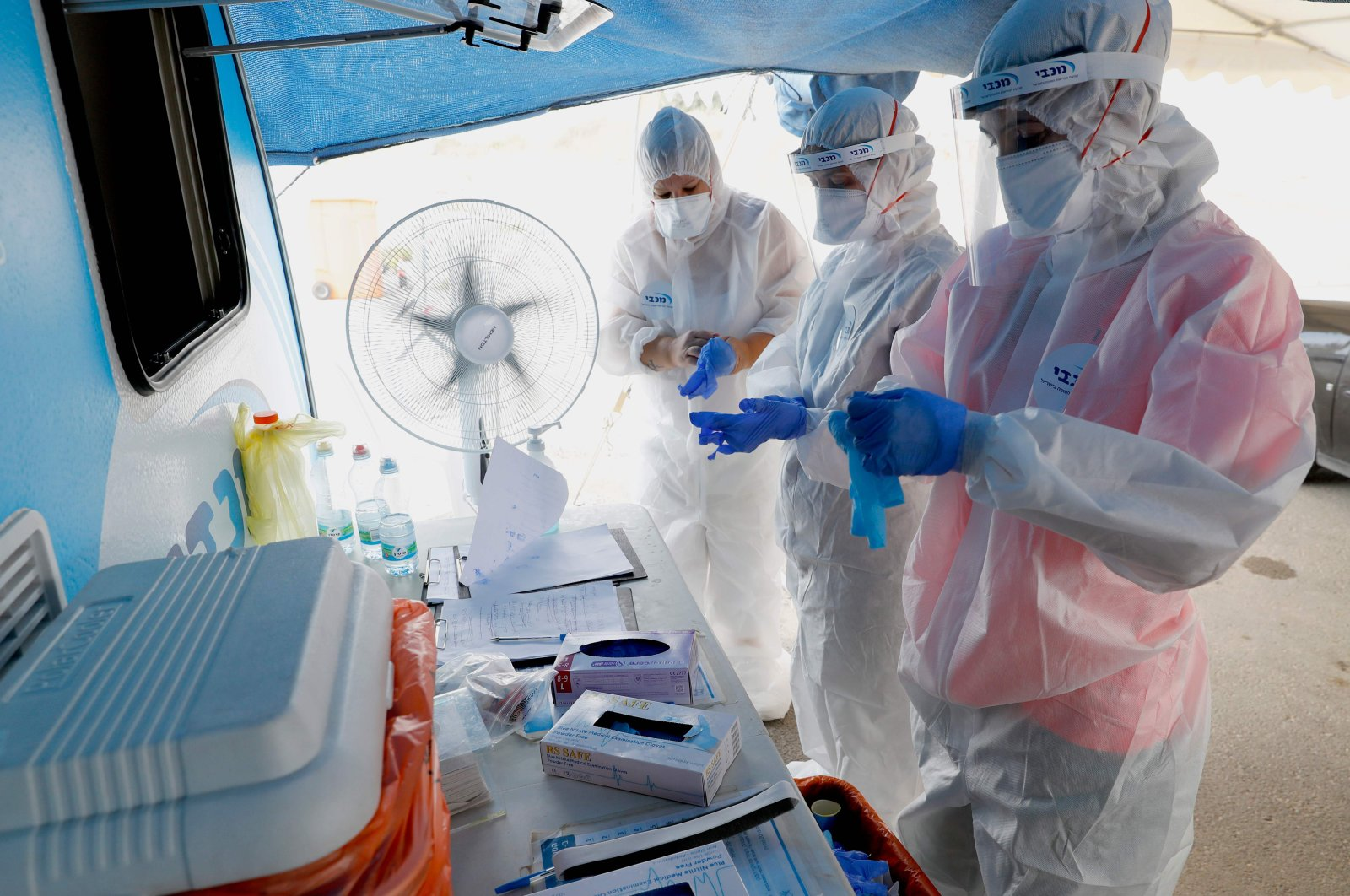 Israeli medical personnel take samples at a drive-thru COVID-19 testing facility in Ramat Hasharon in the suburbs of Tel Aviv, July 6, 2020. (AFP Photo)