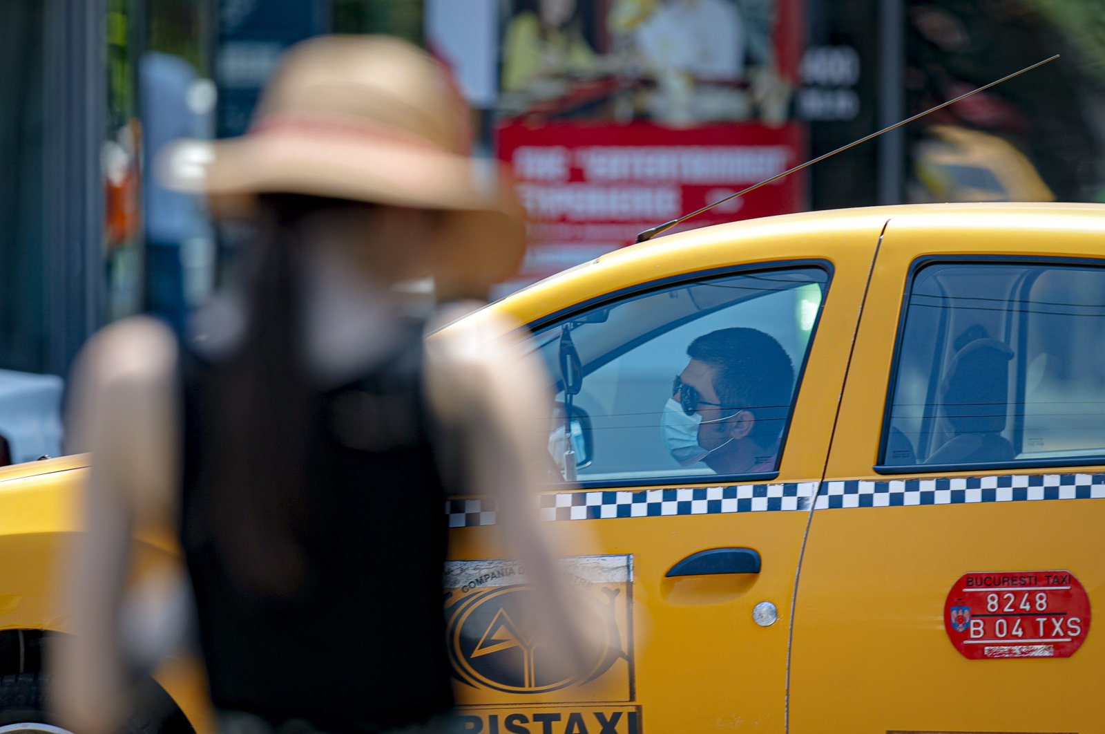 A taxi driver wears a mask in Bucharest, Romania, July 3, 2020. (AP Photo)
