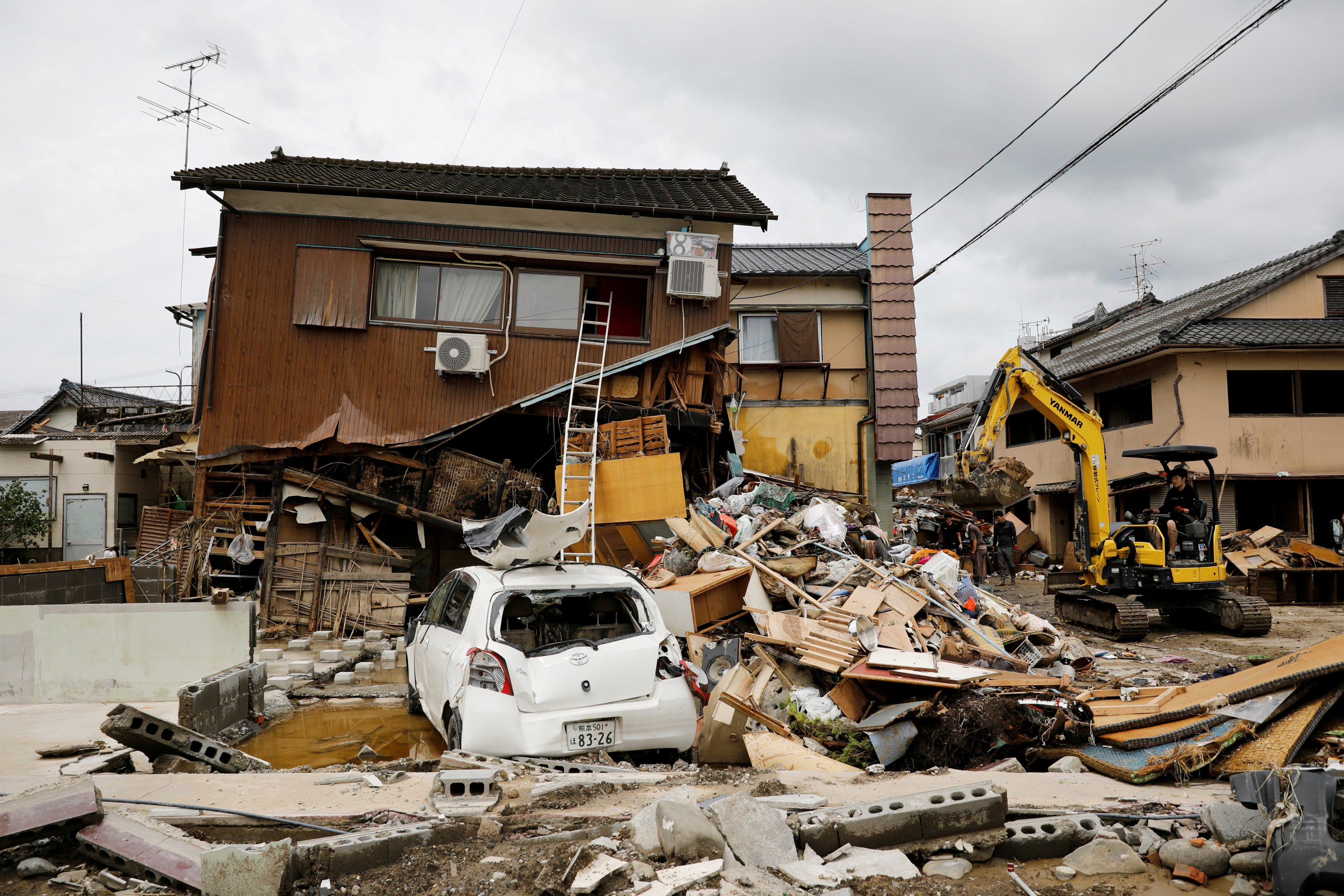 An excavator clears up debris next to a damaged house after floods caused by torrential rain in Hitoyoshi, Kumamoto Prefecture, southwestern Japan, July 8, 2020. (Reuters Photo)