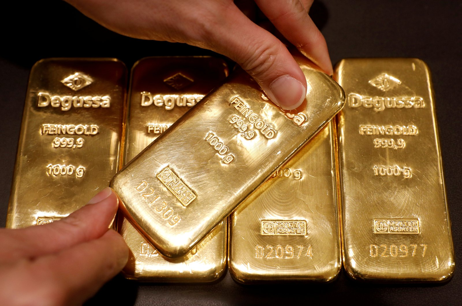 In this June 16, 2017, file photo, an employee shows gold bullions at Degussa shop in Singapore. (Reuters Photo)