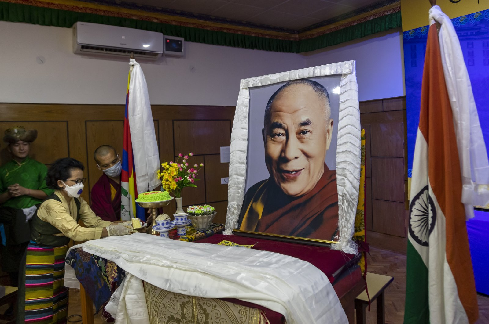 An exile Tibetan offers a piece of cake to a portrait of her spiritual leader the Dalai Lama to mark her leader's 85th birthday in Dharmsala, India, July 6, 2020. (AP Photo)