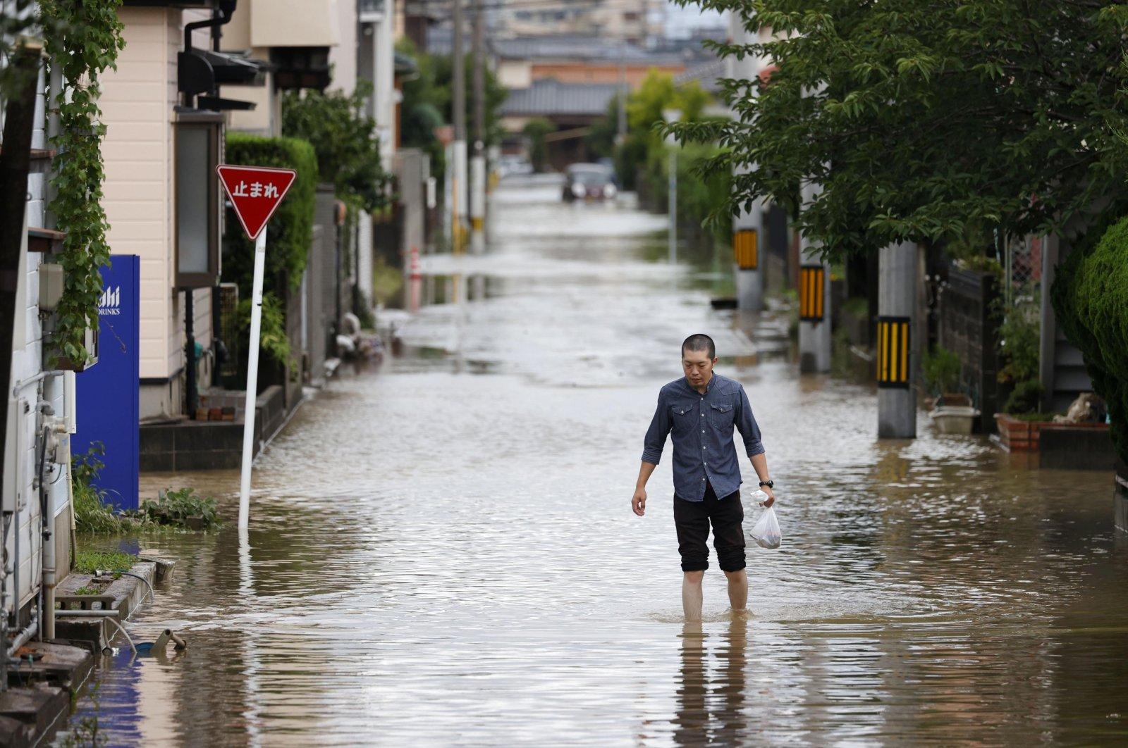 A man walks through a flooded road following heavy rain in Omuta, Fukuoka prefecture, southern Japan Tuesday, July 7, 2020. Floodwaters flowed down streets in southern Japanese towns hit by heavy rains. (Juntaro Yokoyama/Kyodo News via AP)