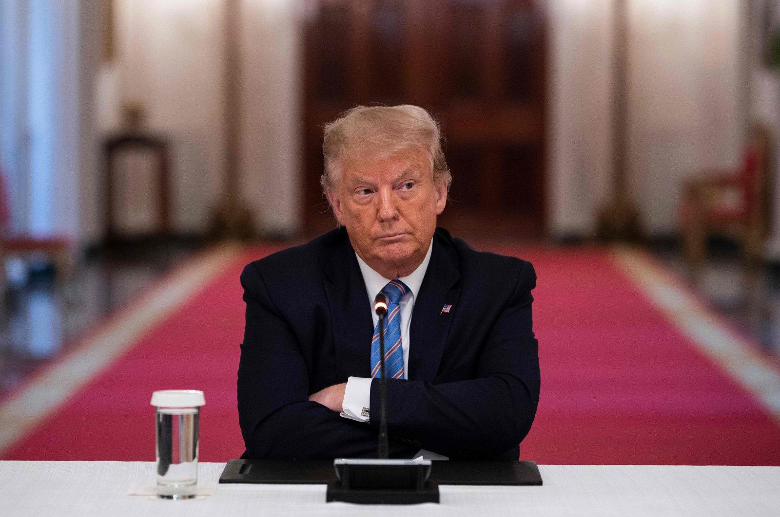 U.S. President Donald Trump sits with his arms crossed during a roundtable discussion on the Safe Reopening of America's Schools during the coronavirus pandemic, in the East Room of the White House in Washington, D.C. on July 7, 2020. (AFP Photo)
