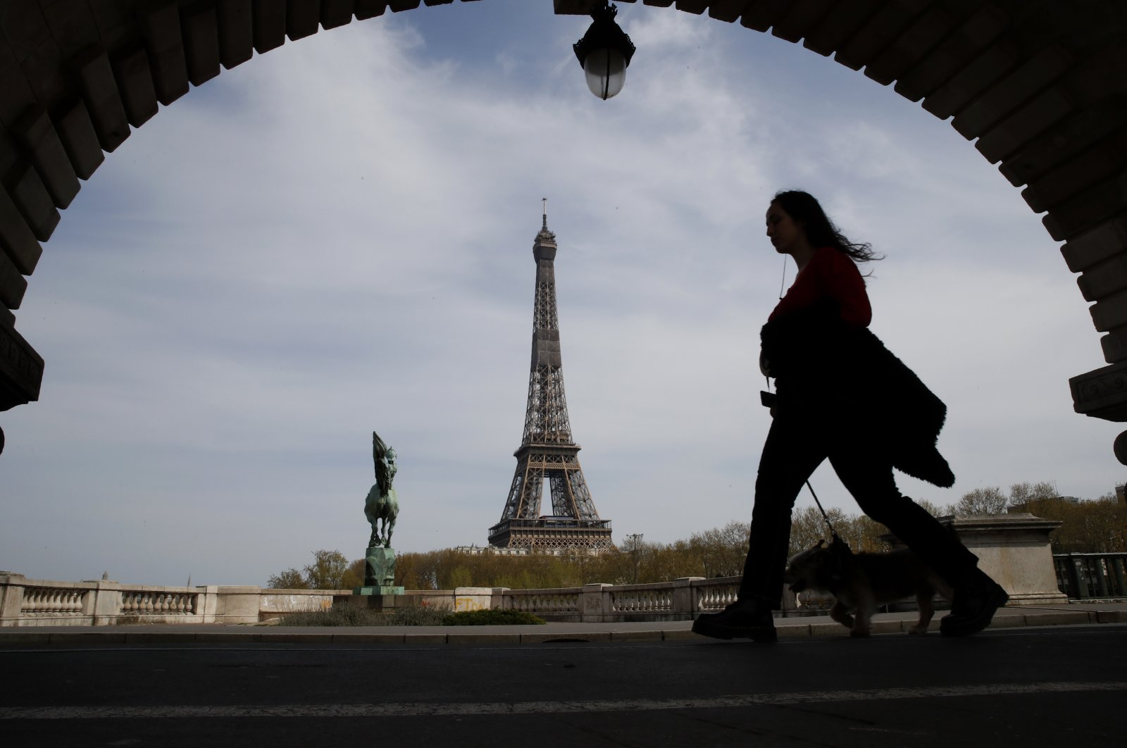 A woman walks her dog on a Paris bridge, with the Eiffel tower in background, during a nationwide confinement to counter the COVID-19 in Paris, France, April 7, 2020. (AP Photo)