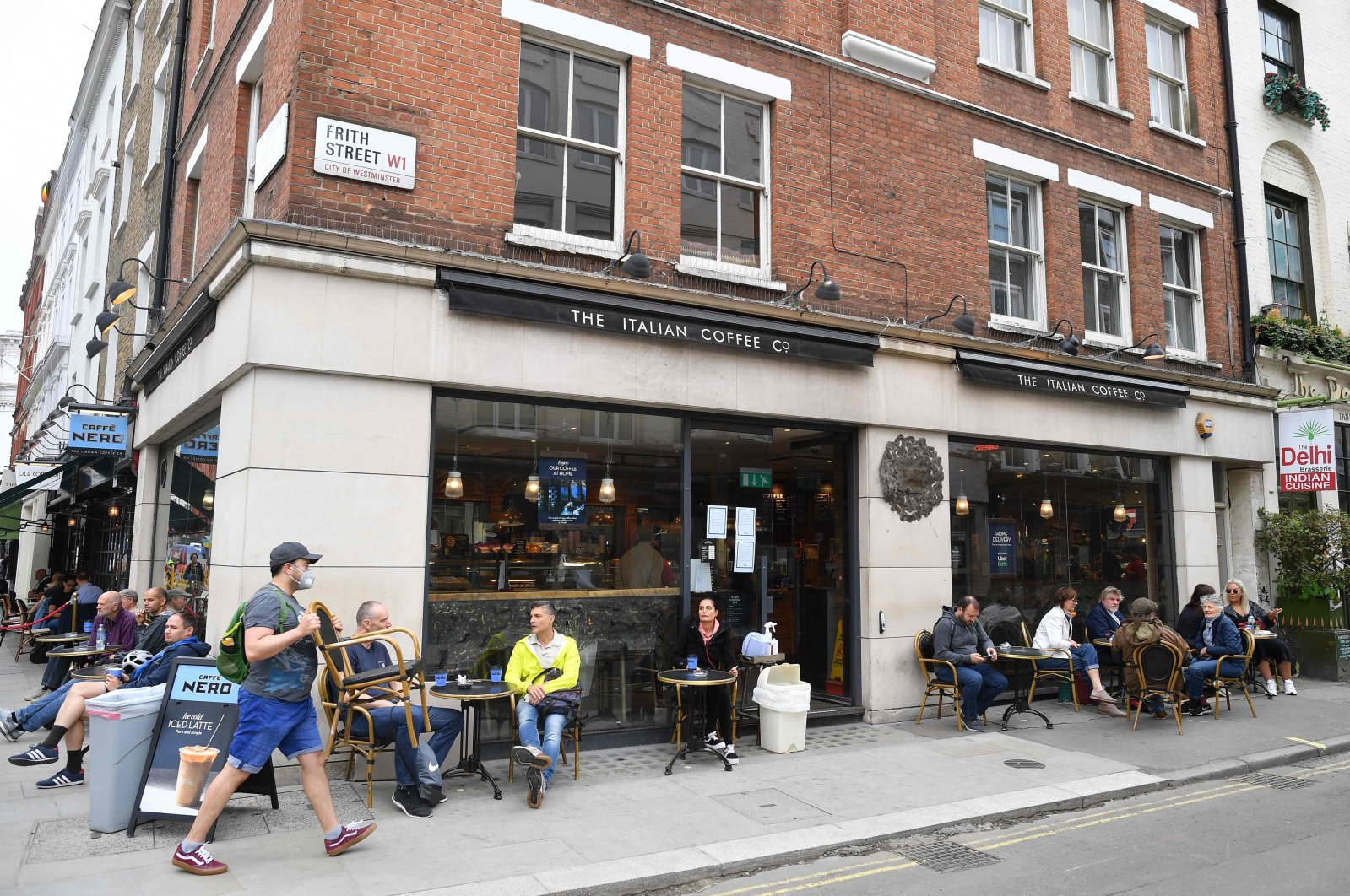 A man moves a chair to sit down outside a branch of Cafe Nero in Frith Street in London, July 4, 2020. (AFP Photo)