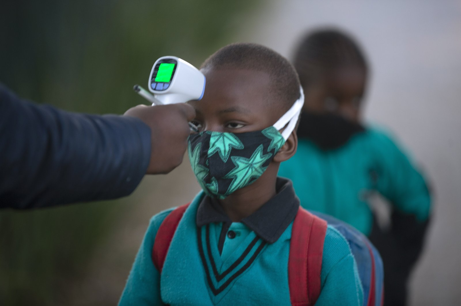 A pupil's temperature is checked on returning to school, Johannesburg, July 7, 2020. (AP Photo)