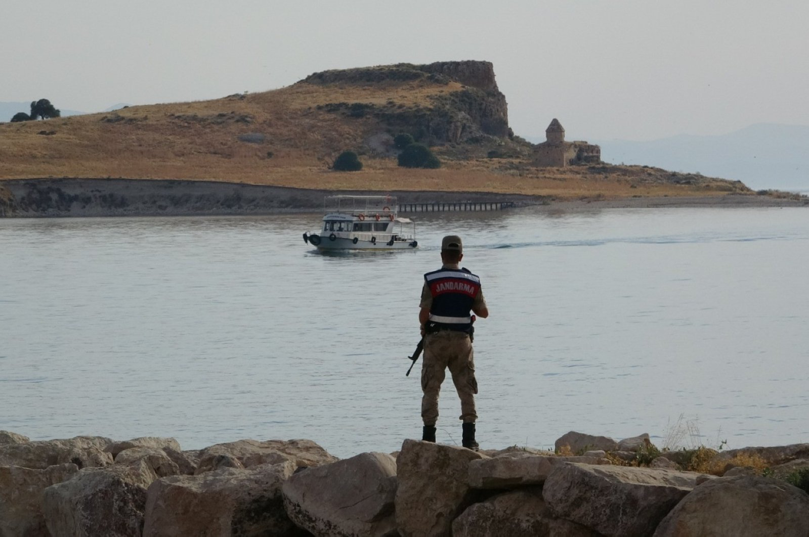 A Turkish gendarmerie soldier watches as the sank migrant boat is being taken out from the underwater in Lake Van, July 8, 2020. (IHA)