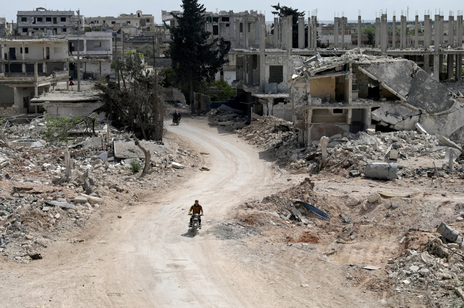 A man rides a motorbike past damaged buildings in the opposition-held town of Nairab, Idlib region, Syria April 17, 2020. (REUTERS Photo)