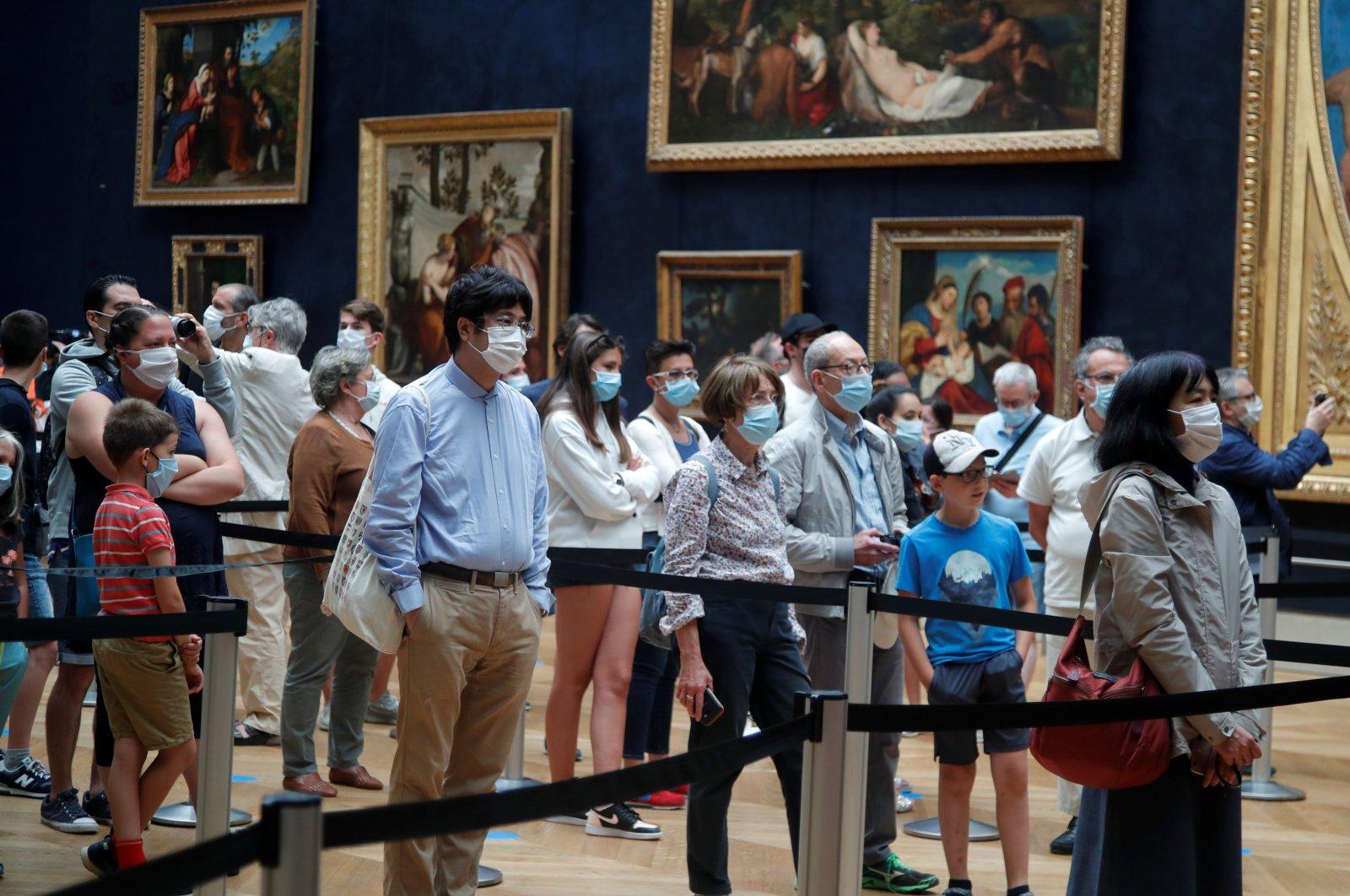 "Visitors, wearing protective face masks, queue to see the painting ""Mona Lisa"" (La Joconde) by Leonardo Da Vinci at the Louvre museum, Paris, July 6, 2020. (REUTERS Photo)"
