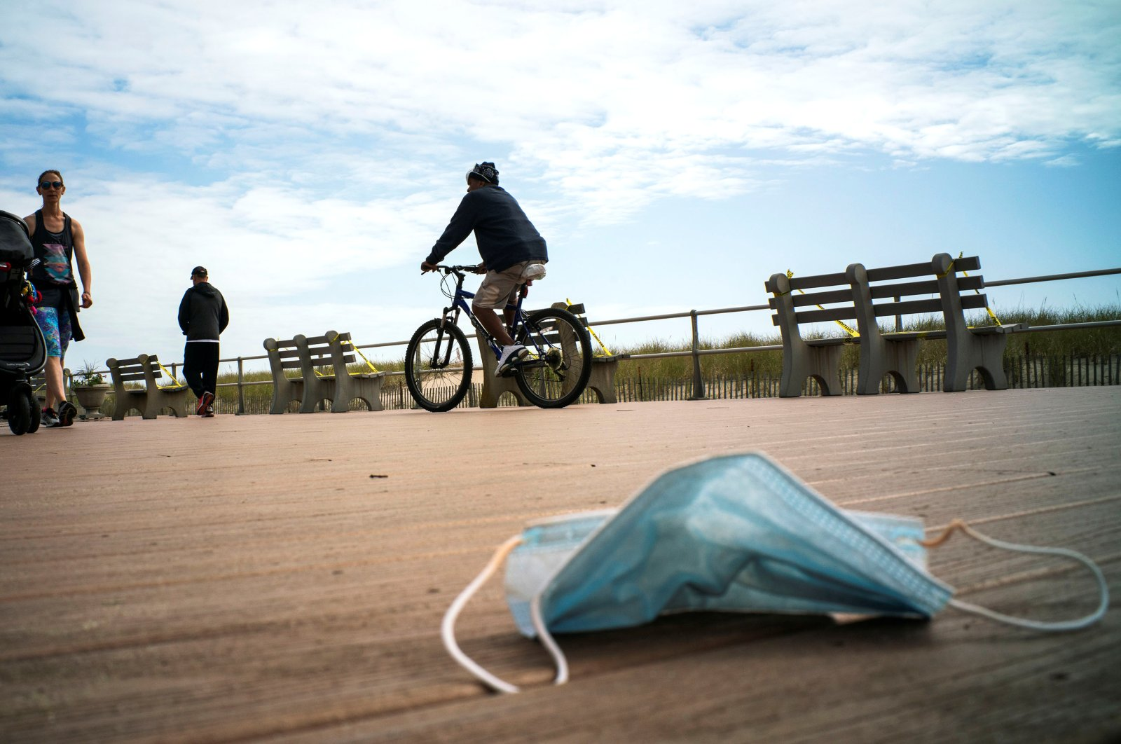 A face mask is seen on the floor as people walk the boardwalk of Ocean Grove beach on the first day that New Jersey beaches were reopened ahead of the Memorial Day weekend following the outbreak of the coronavirus in Ocean Grove, New Jersey, U.S., May 22, 2020. (Reuters Photo)