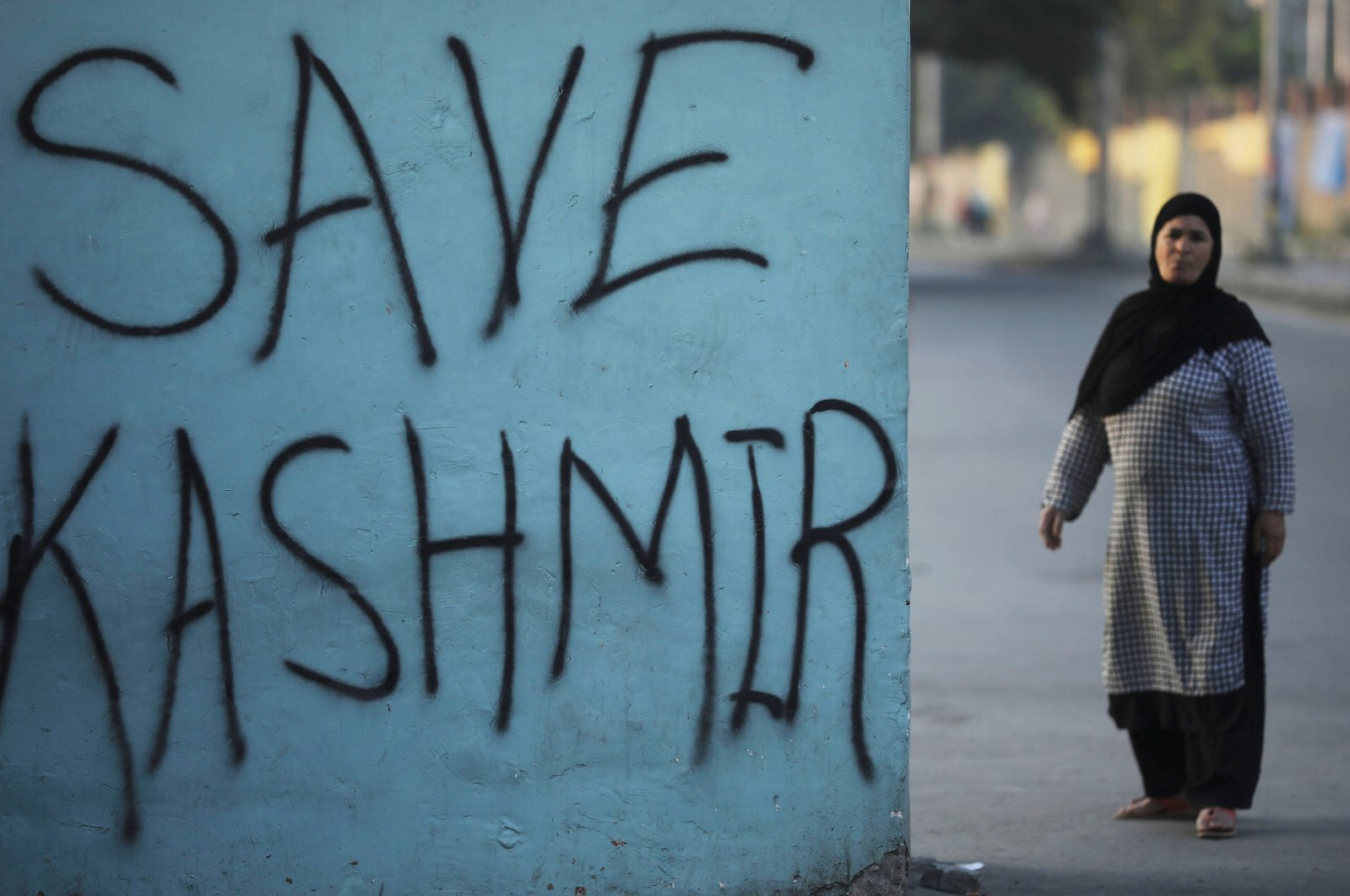 A Kashmiri woman stands next to a graffiti written on a wall during restrictions, Srinagar, Sept. 15, 2019. (REUTERS Photo)