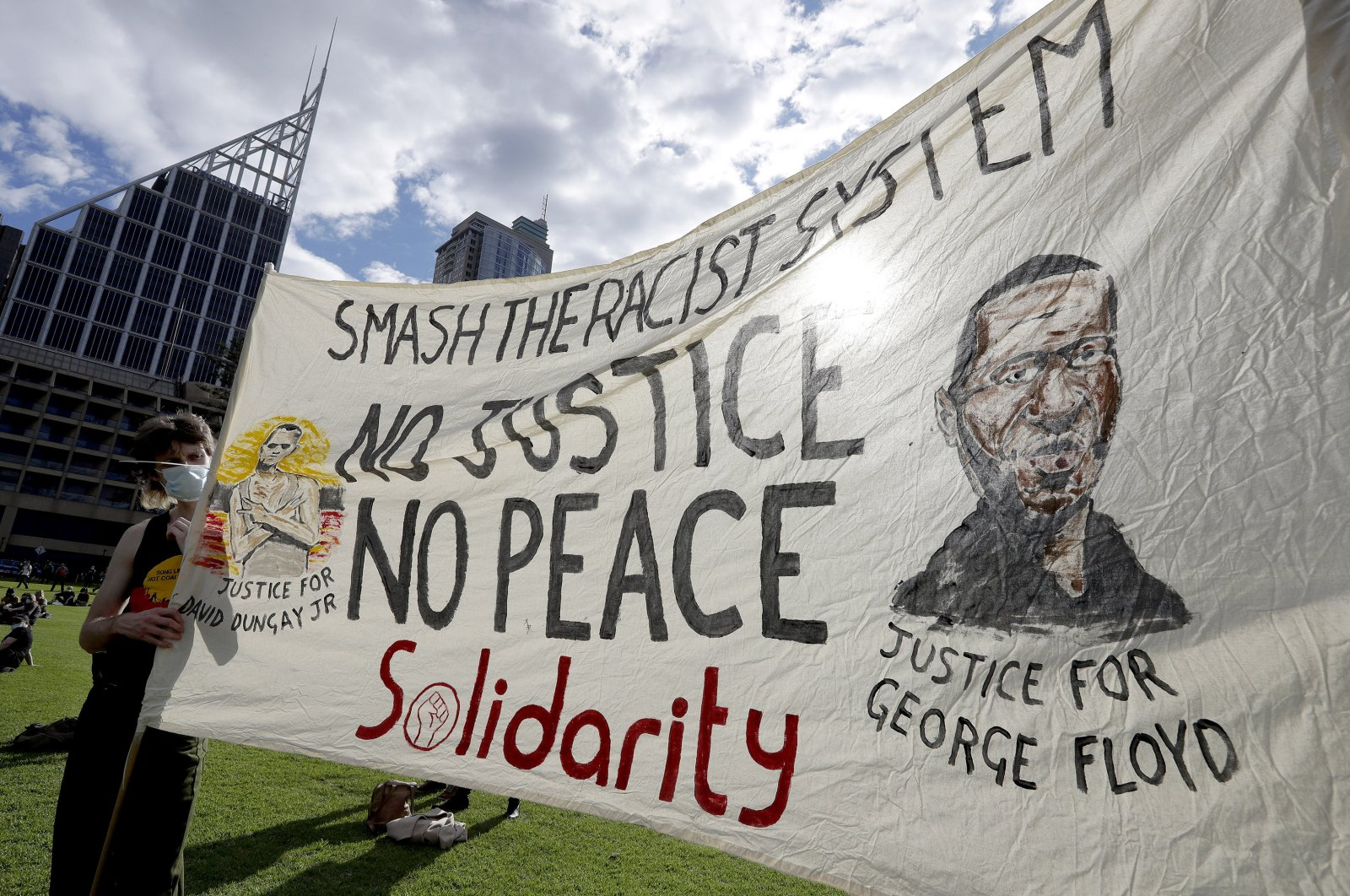 A man holds a banner showing George Floyd as thousands gather at a rally supporting the Black Lives Matter and Black Deaths in Custody movements in Sydney, Sunday, July 5, 2020. (AP Photo)