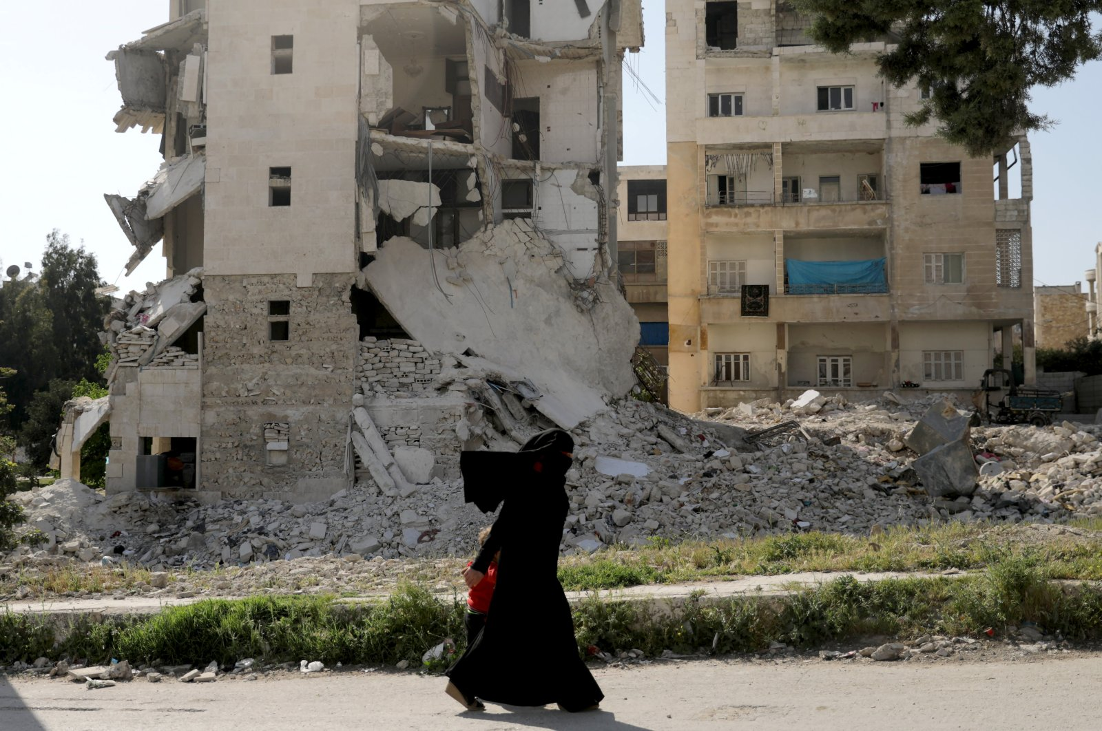A woman walks past damaged buildings with her child in the rebel-held Idlib city, Syria April 19, 2020. (Reuters File Photo)