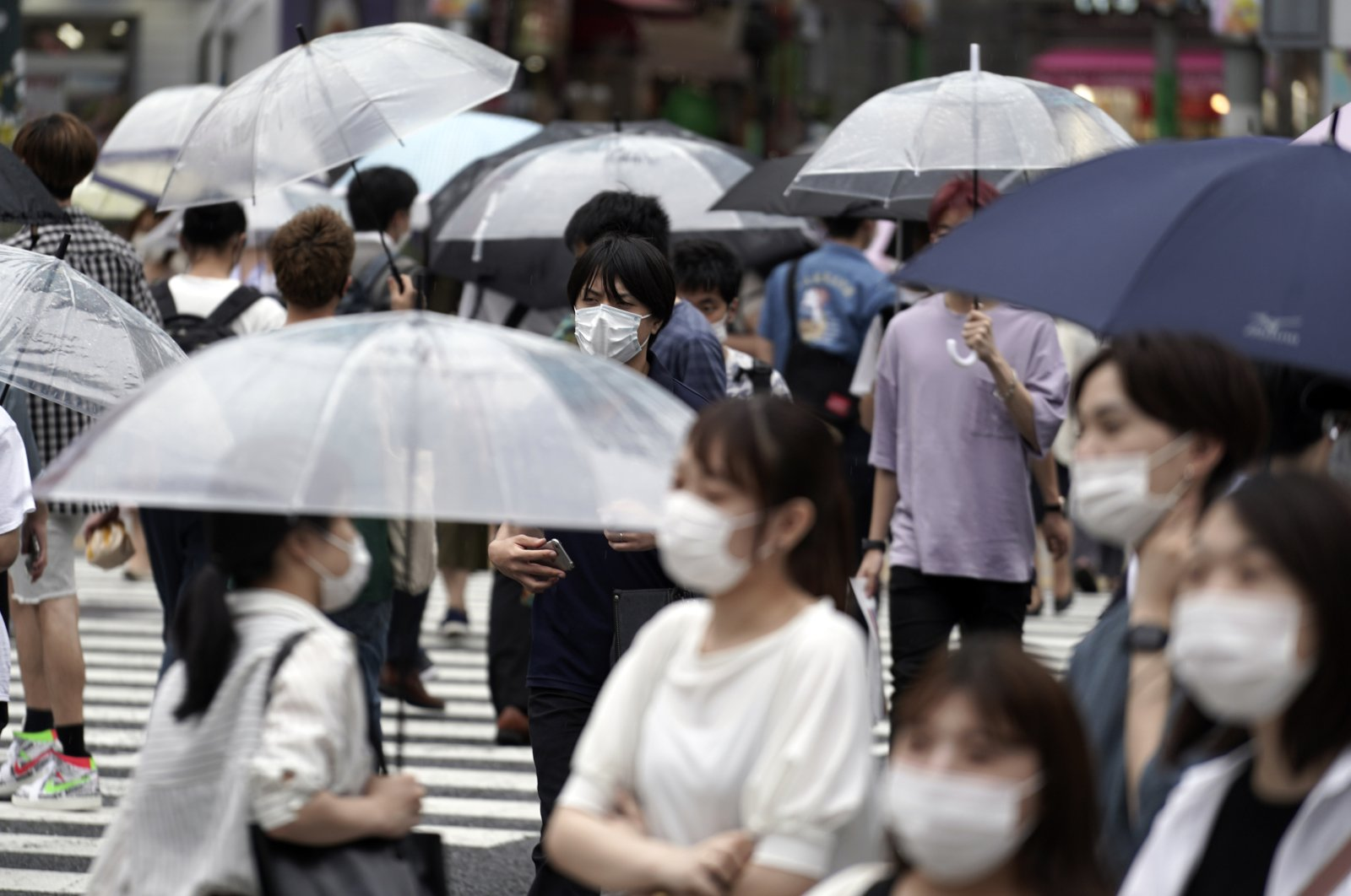 People wearing protective face masks to help curb the spread of the coronavirus walk at a Shibuya pedestrian crossing, Tokyo, Japan, July 9, 2020. (AP Photo)