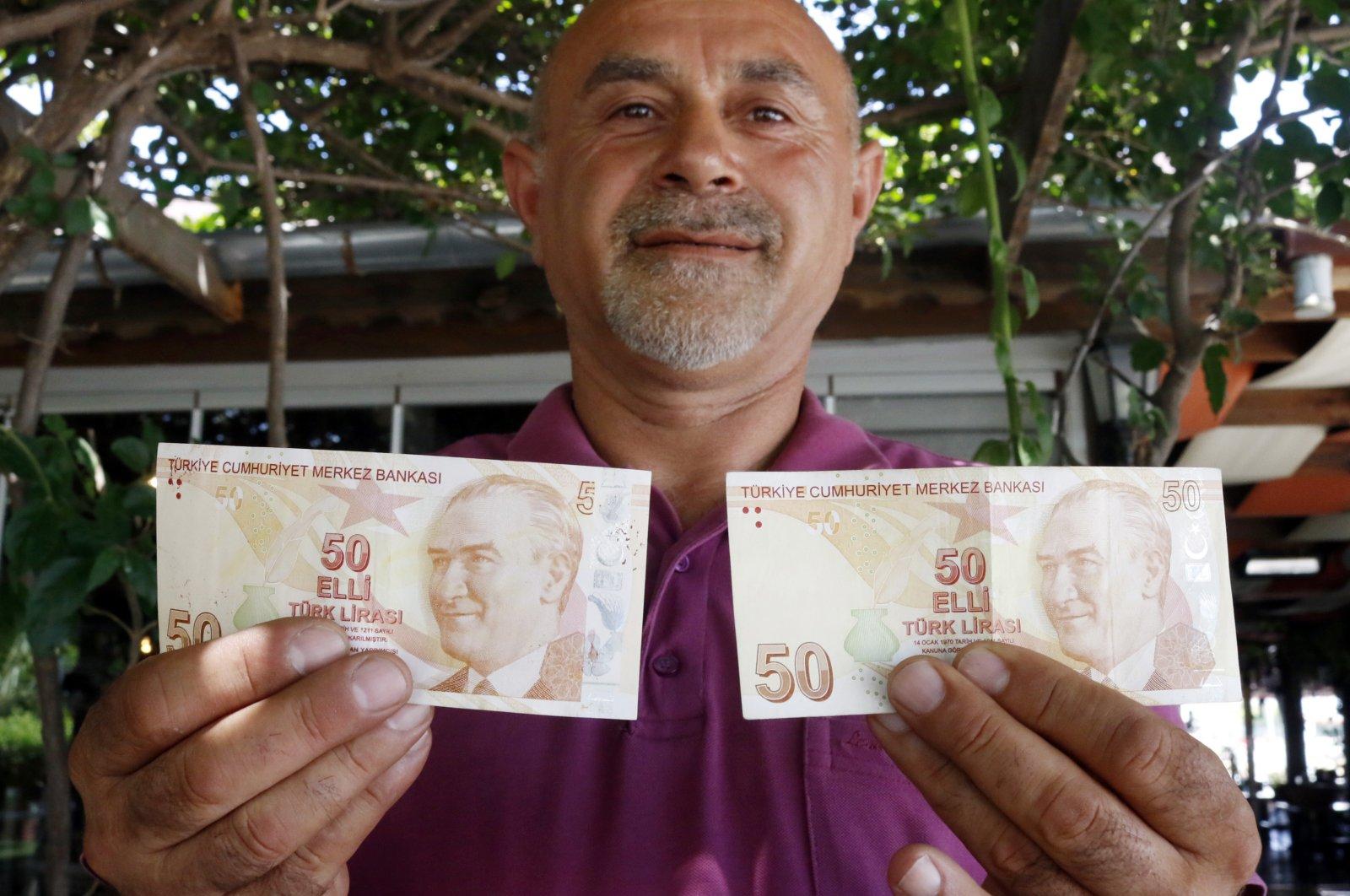 Mustafa Şahin holds up his misprinted TL 50 bill (L) and a normal one, Antalya, Turkey, July 9, 2020. (DHA Photo)