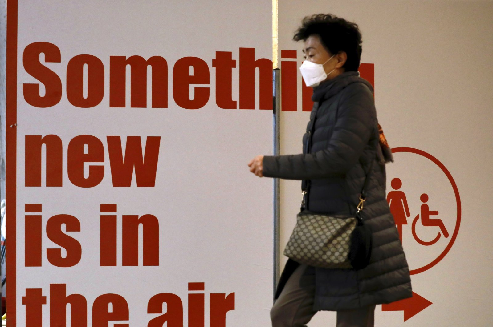 A tourist from South Korea wears a protective mask while waiting for a flight back to South Korea at the Ben Gurion airport near Tel Aviv, Israel, Feb. 24, 2020. (AP Photo)