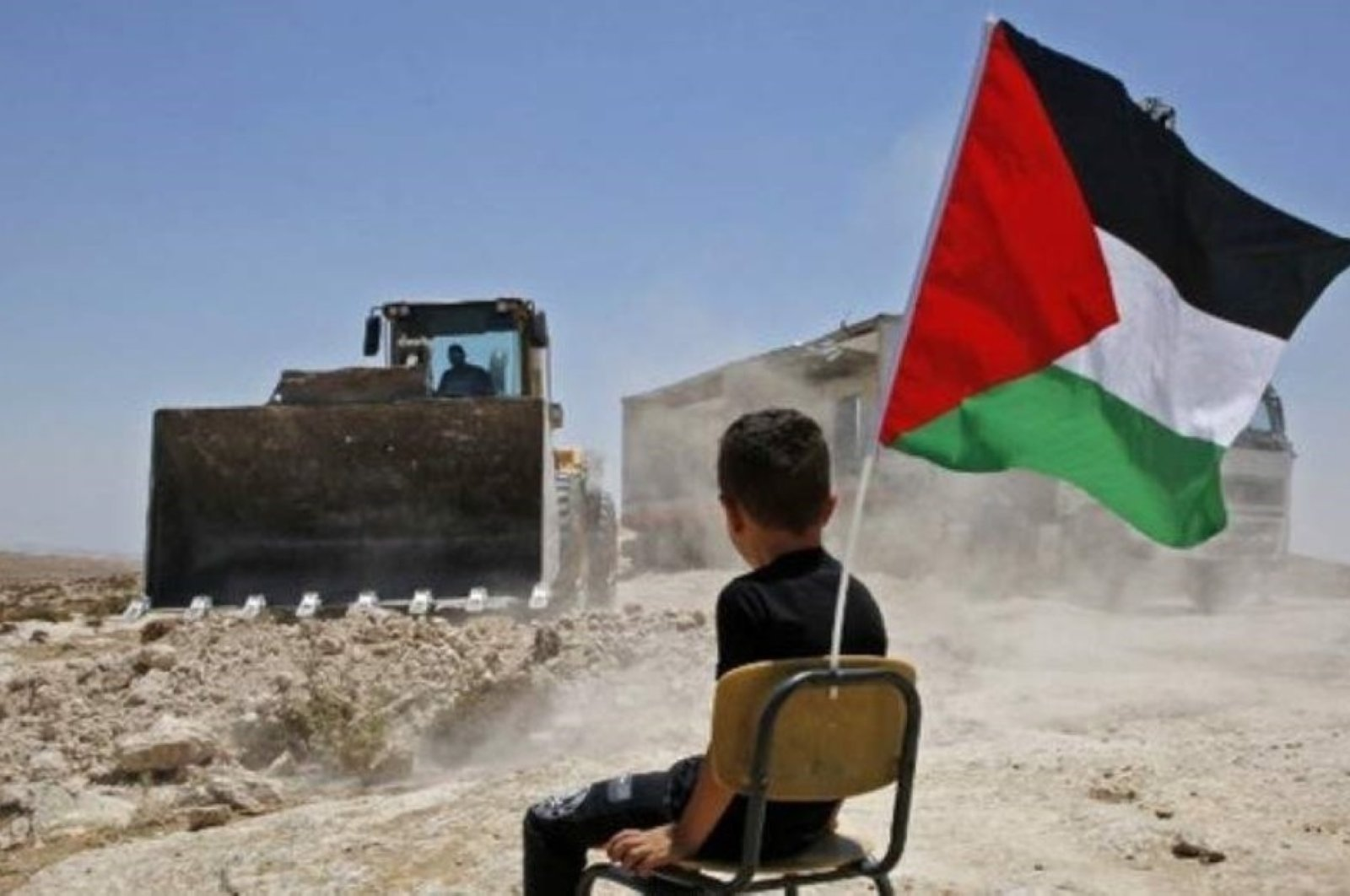 A Palestinian boy sits on a chair with a national flag as Israeli authorities demolish a school site in the village of Yatta in the occupied West Bank, July 11, 2018. (AFP Photo)
