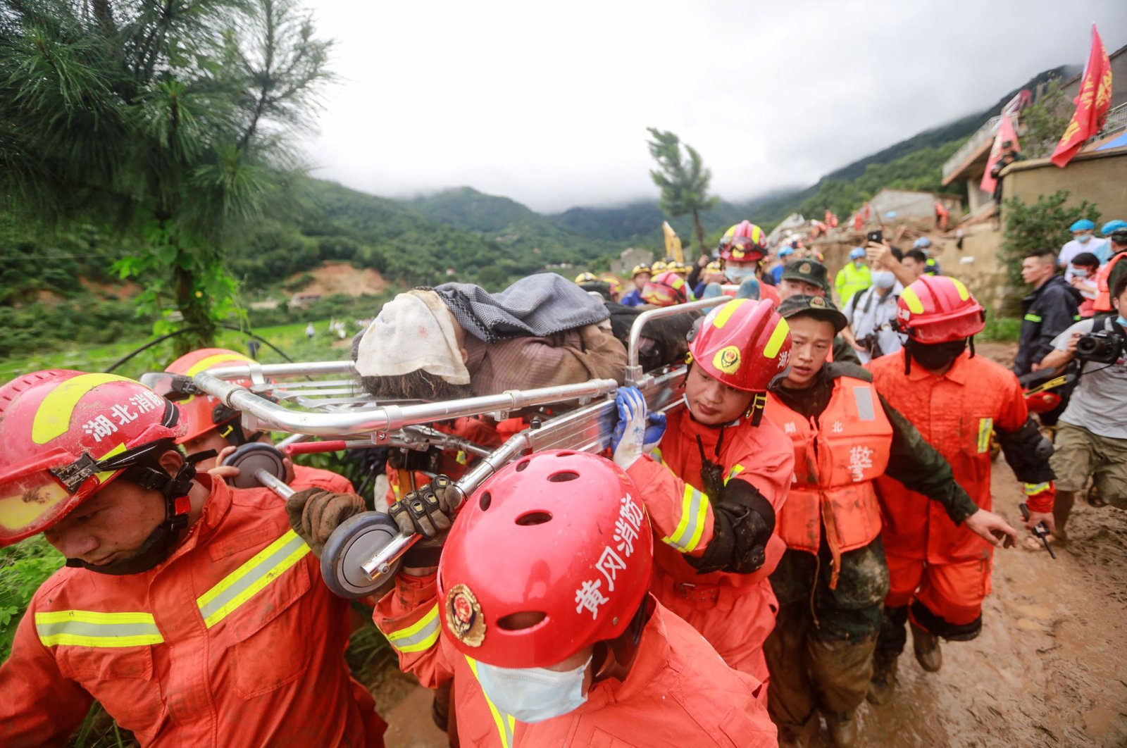 Rescuers carry an injured person at the scene of a landslide in Huangmei county, Huanggang city, in China's central Hubei province, July 8, 2020. (AFP Photo)