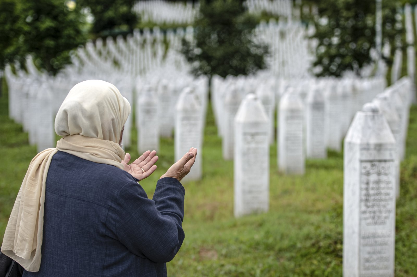 A woman prays at the memorial cemetery in Potocari, near Srebrenica, Bosnia-Herzegovina, July 7, 2020. (AP Photo)