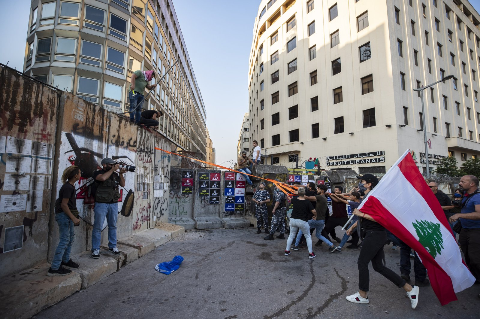 Anti-government protesters try to remove a concrete wall that was installed by security forces to prevent them from reaching the government palace in Beirut, Lebanon, July 2, 2020. (AP Photo)