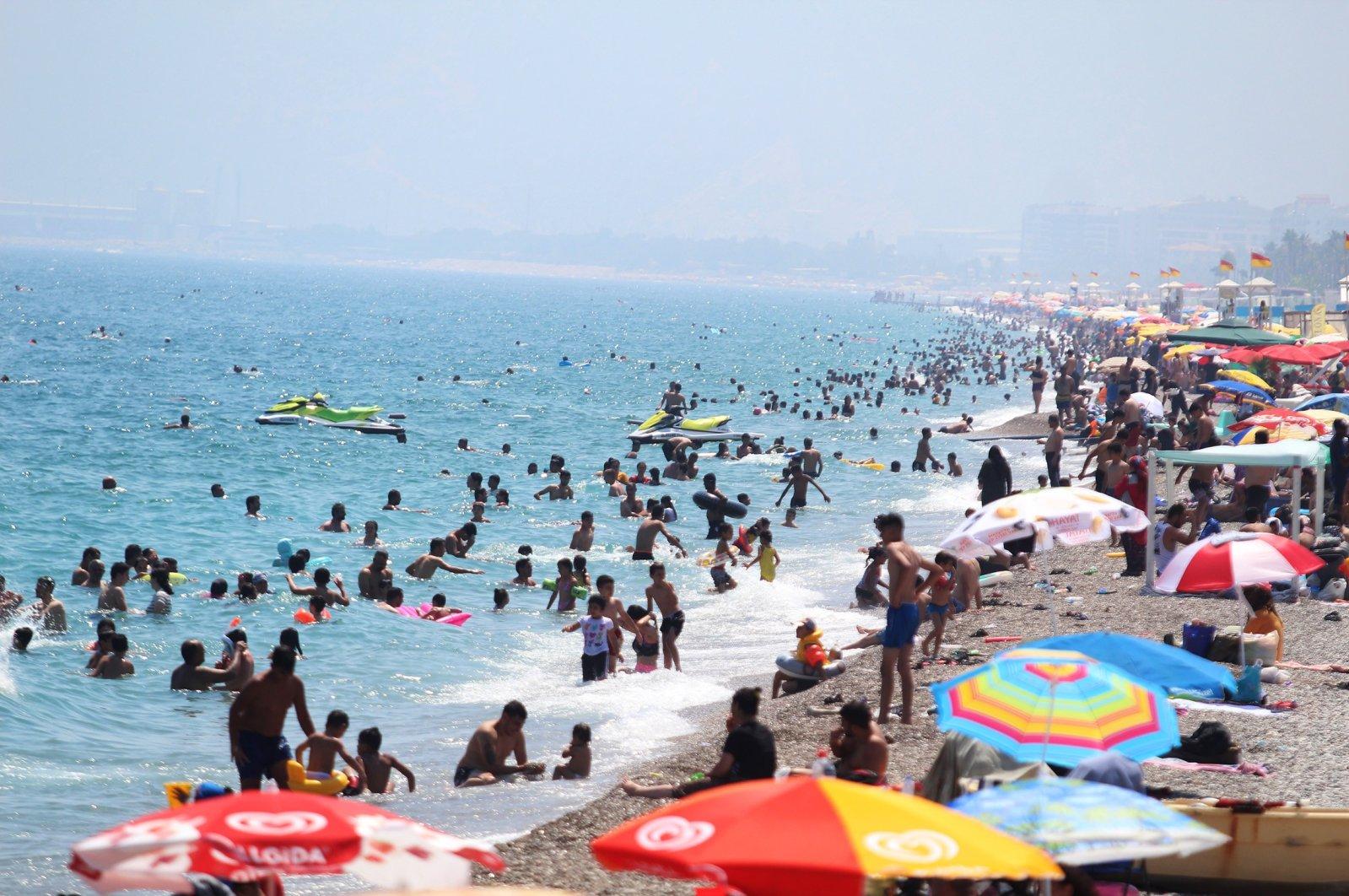 People are seen on Konyaaltı beach, amid the COVID-19 outbreak, in the southern resort city of Antalya, Turkey, July 5, 2020. (IHA Photo)