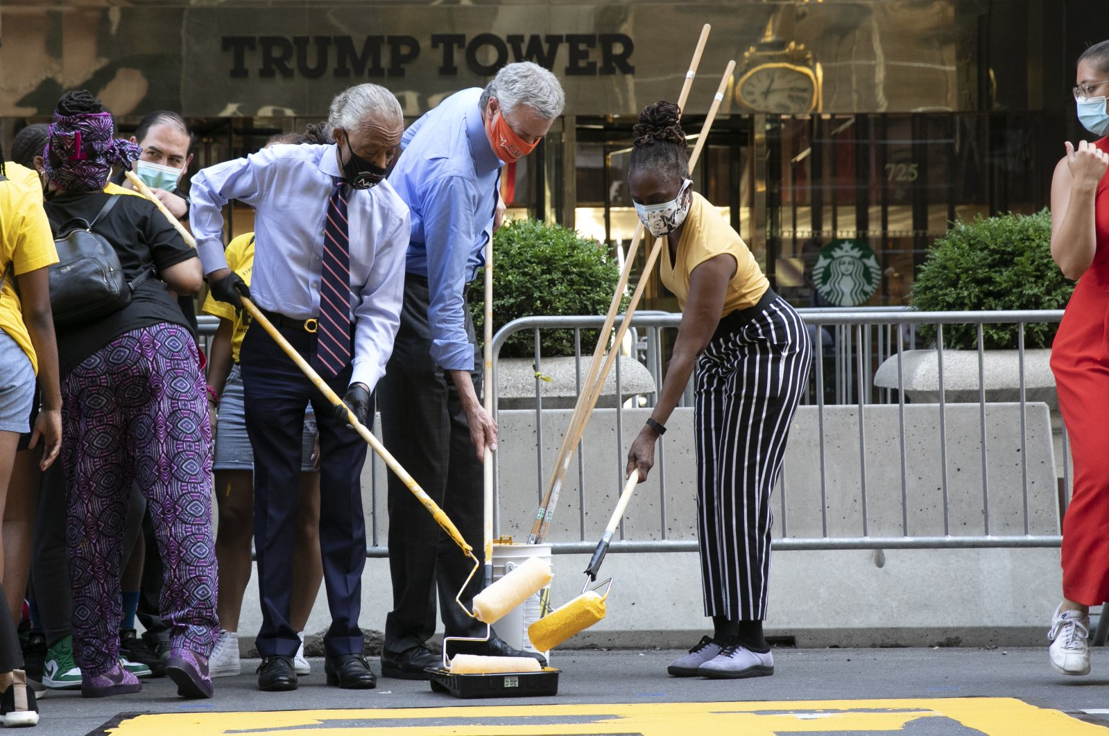Mayor Bill de Blasio, center, is joined by Rev. Al Sharpton, left, and the mayor's wife Chirlane McCray, as they prepare to paint Black Lives Matter on Fifth Avenue in front of Trump Tower, Thursday, July 9, 2020, in New York. (AP Photo)
