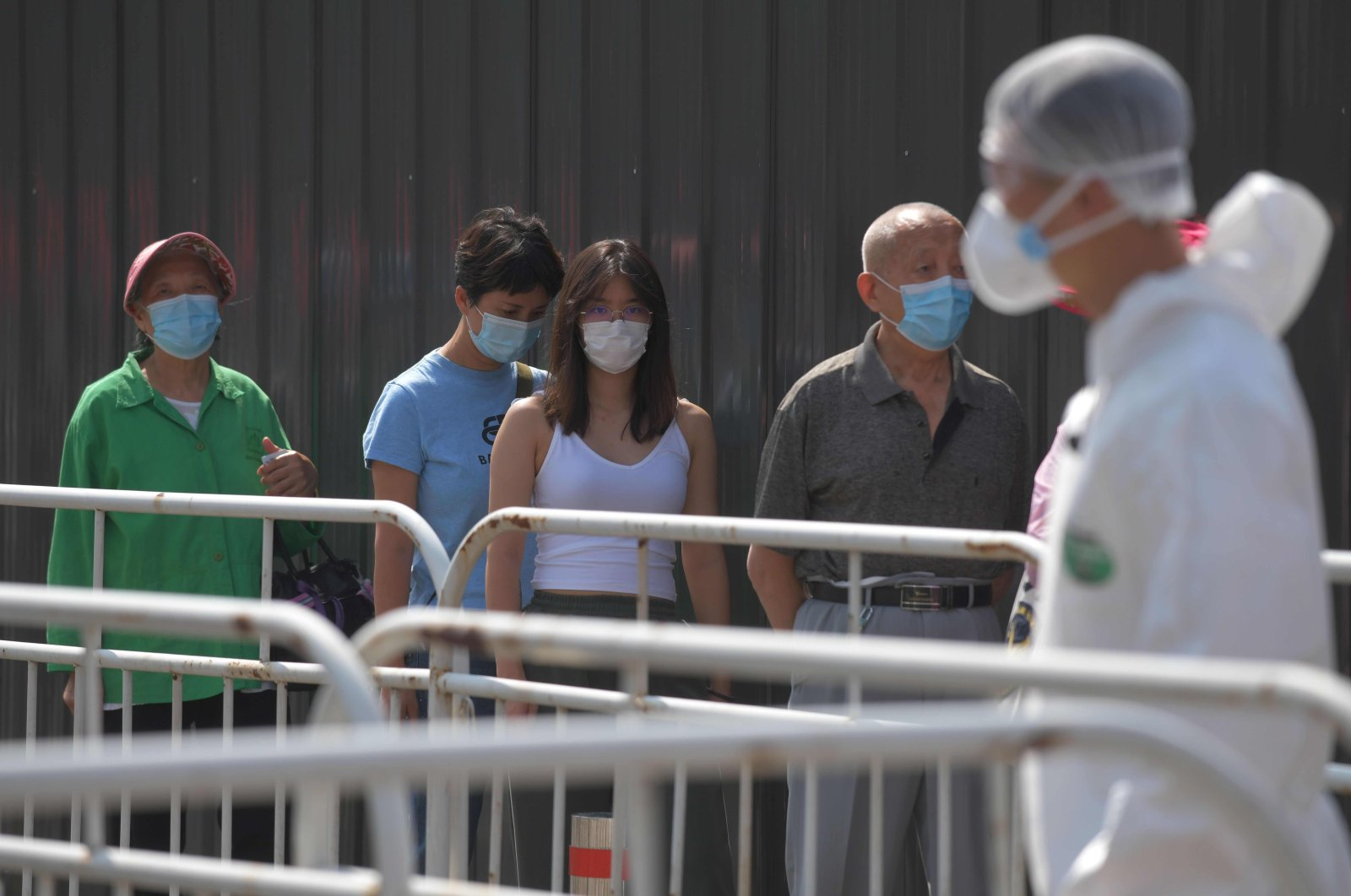 In this file photo people wait in line to undergo COVID-19 coronavirus swab tests at a testing station, Beijing, June 30, 2020. (AFP Photo)