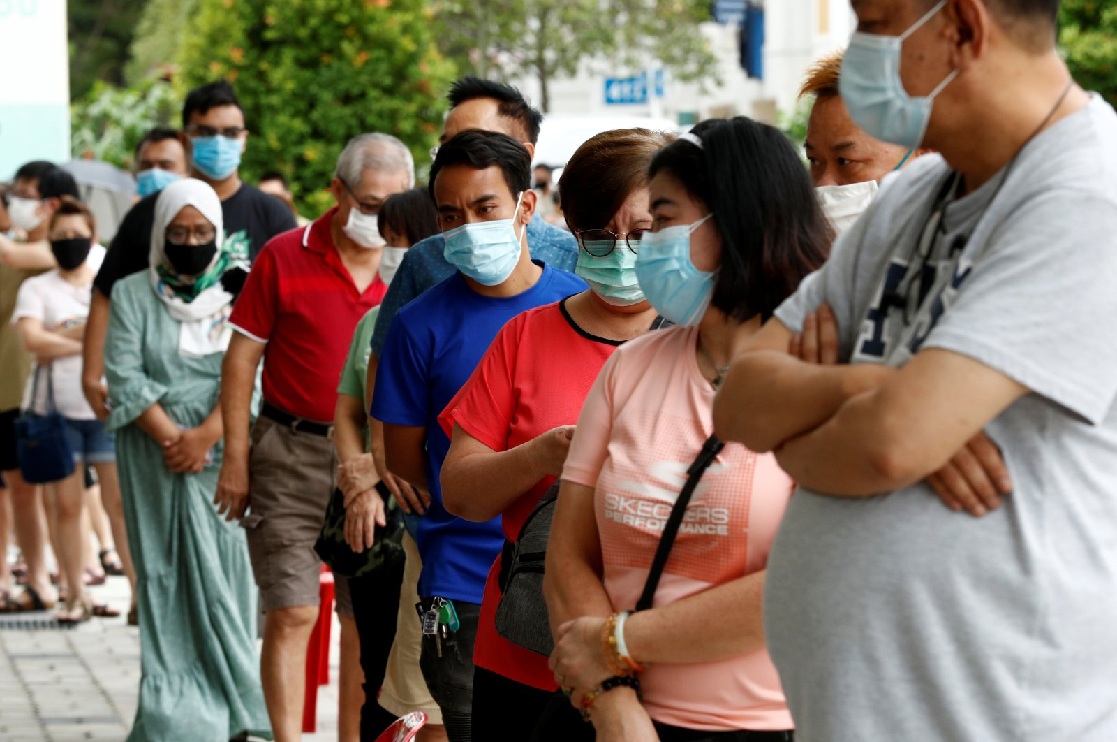 Voters wear protective face masks as they queue up at a polling station during Singapore's general election, amid the coronavirus disease (COVID-19) outbreak, in Singapore July 10, 2020.  (Reuters Photo)