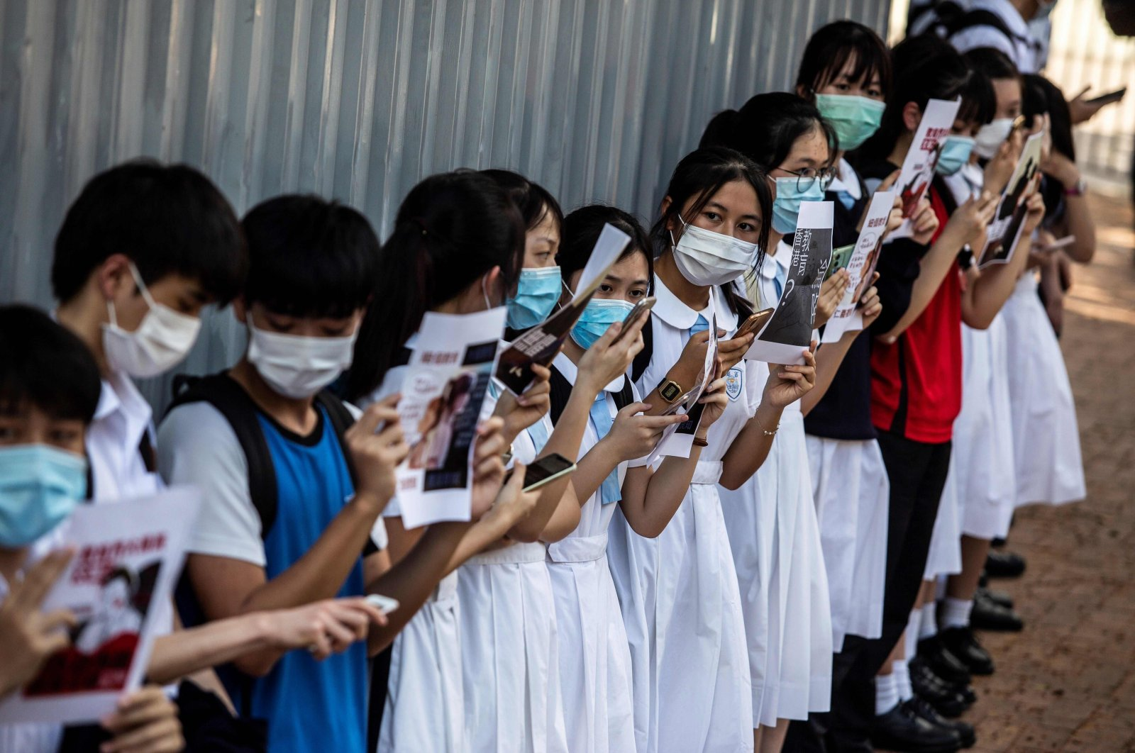 School students hold signs during a pro-democracy protest near their school in Hong Kong, June 12, 2020. (AFP Photo)