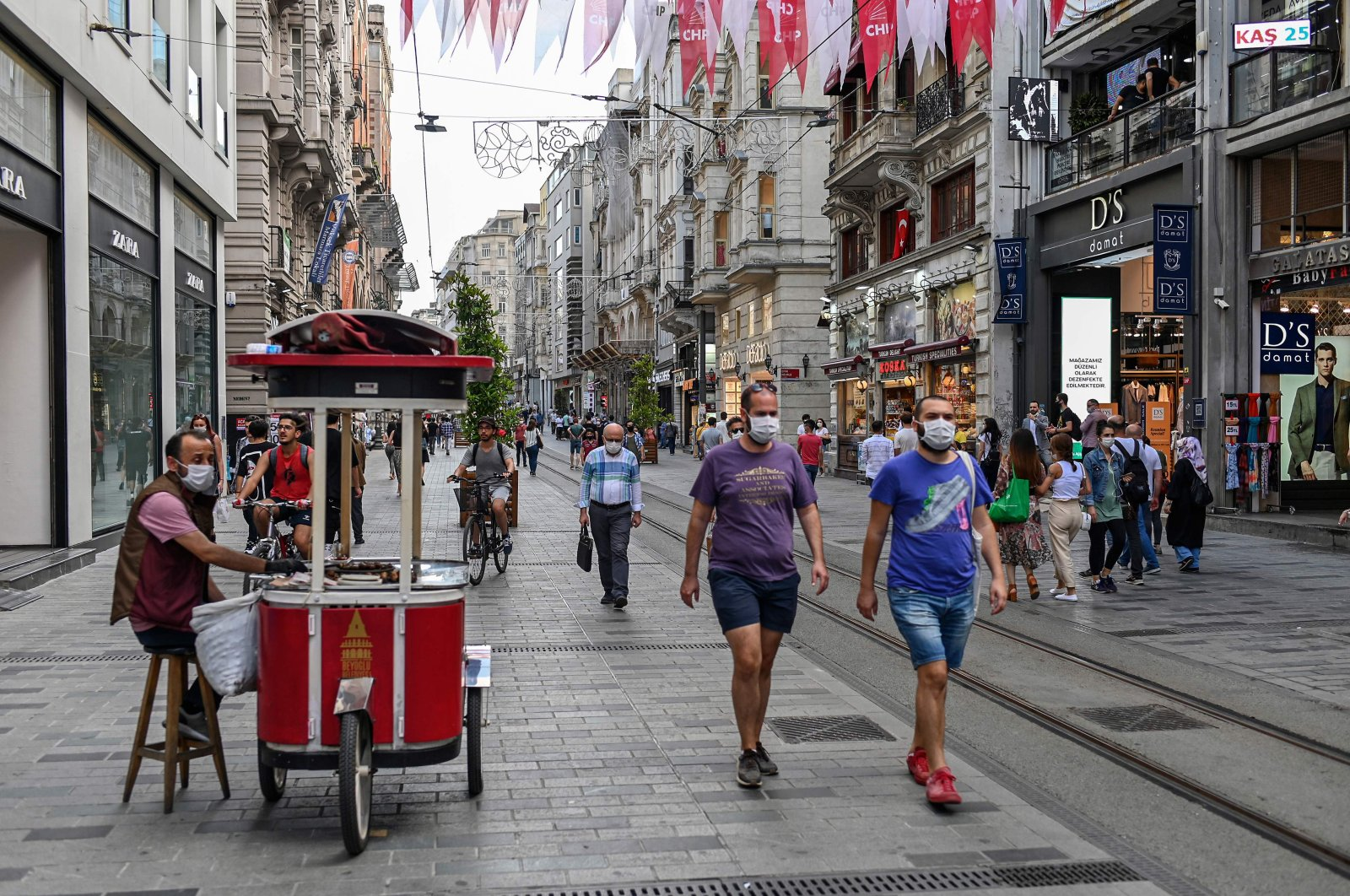 People wearing protective face masks walk on the popular shopping avenue Istiklal, in Istanbul, June 25, 2020. (AFP Photo)