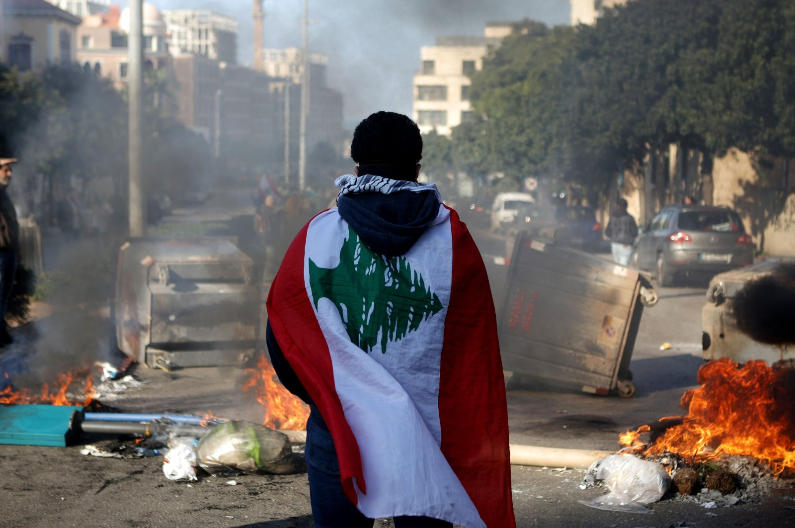 A Lebanese anti-government protester, wrapped in a national flag, stands in front of a road blocked with burning tires and overturned garbage dumpster, Beirut, Jan. 14, 2020. (AFP Photo)