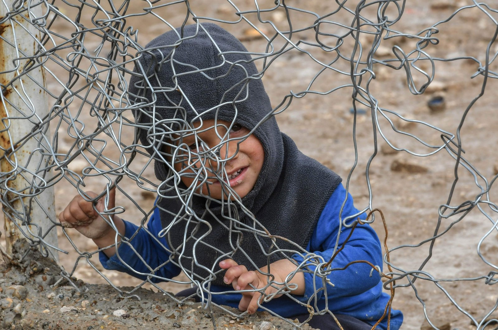 A child sits behind a wire fence in al-Hol camp, which houses relatives of Daesh terror group members, in al-Hasakah governorate in northeastern Syria, March 28, 2019. (AFP Photo)