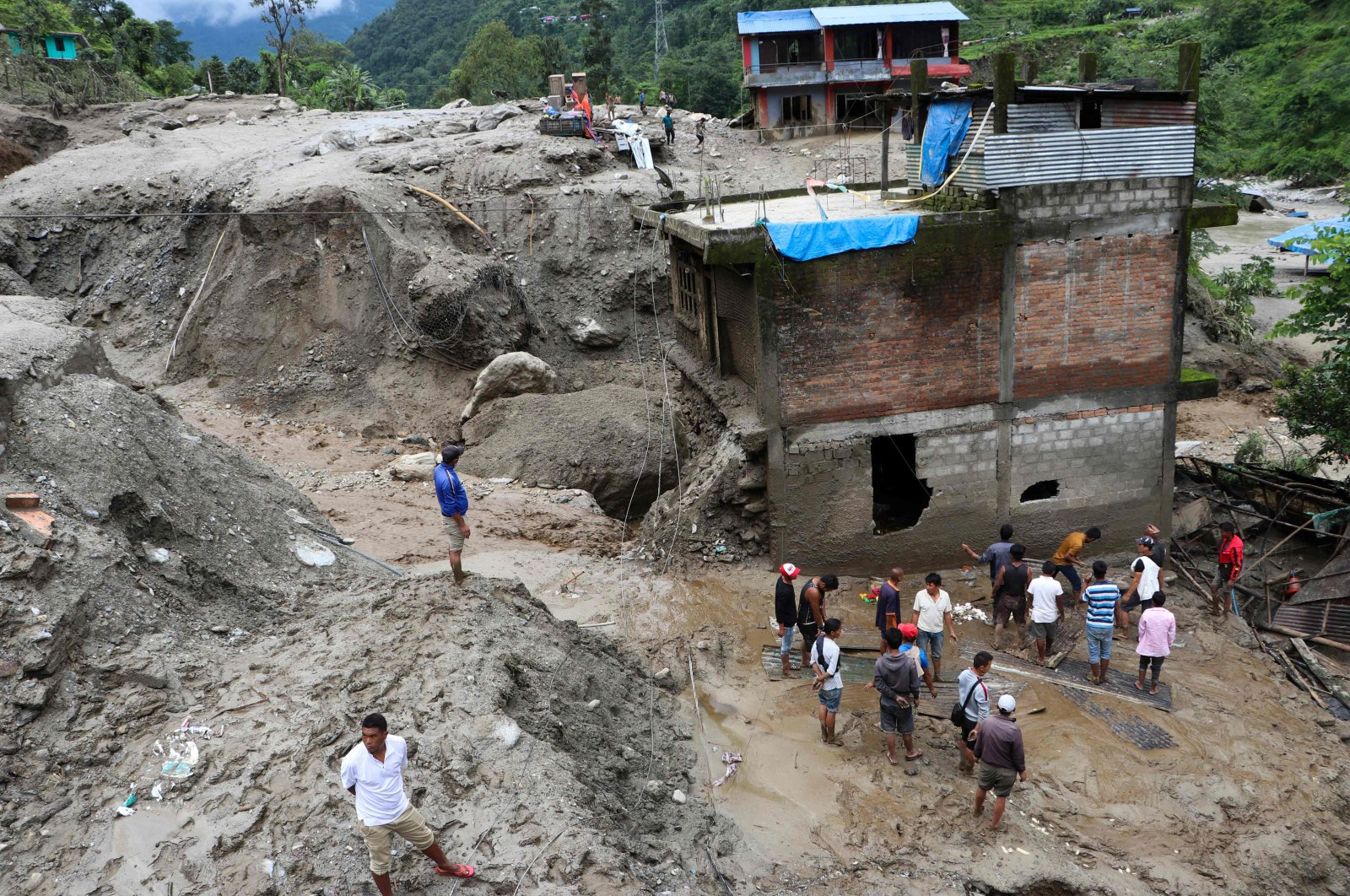 Residents and rescue workers inspect the area outside a house damaged by a landslide and the swell of the Thado-Koshi river due to heavy rains in Jambu village of Sindhupalchok district, some 80 kilometers northeast of Kathmandu, Nepal, July 9, 2020. (AFP Photo)
