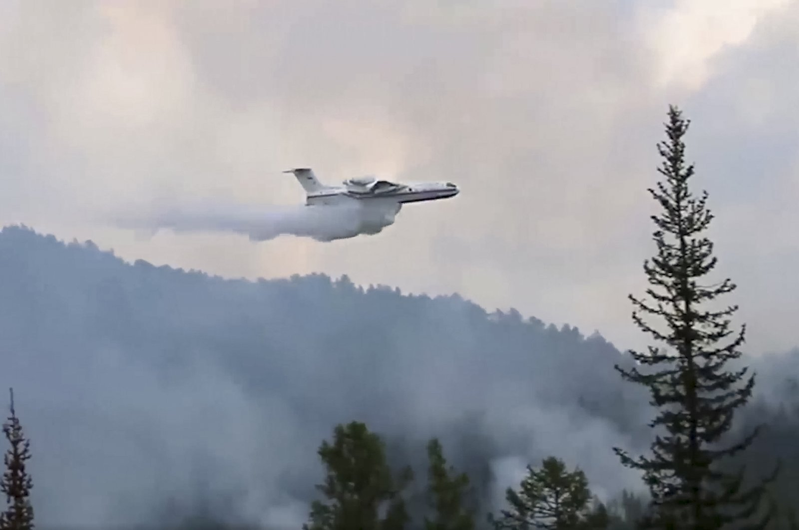 This image taken from video provided by the Russian Emergency Ministry, shows a Russian Emergency Ministry multipurpose amphibious aircraft releasing water to extinguish the fire in the Trans-Baikal National Park in Buryatia, southern Siberia, Russia, July 9, 2020. (Russian Emergency Ministry Press Service via AP)