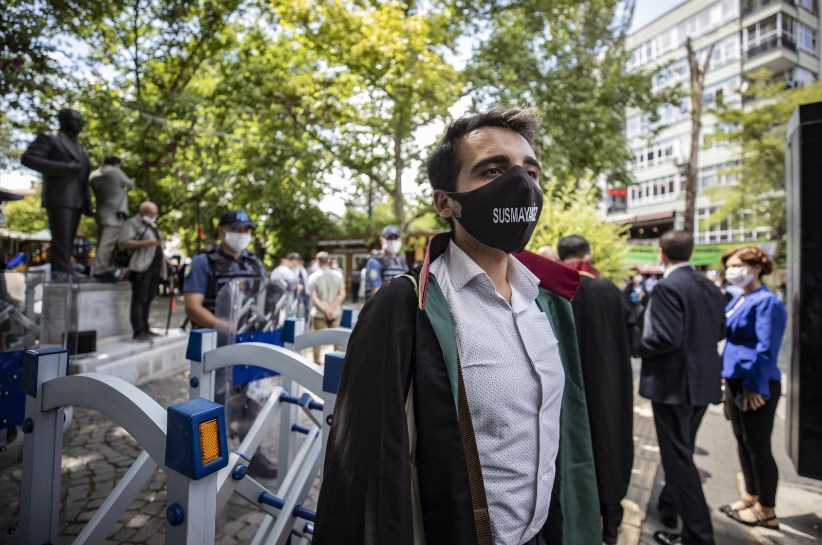 """A lawyer wearing a face mask with the phrase """"We will not be silenced"""" on it stands in protest against the controversial bar regulation in Ankara's Kuğulu Park, Turkey, July 6, 2020. (AA Photo)"""