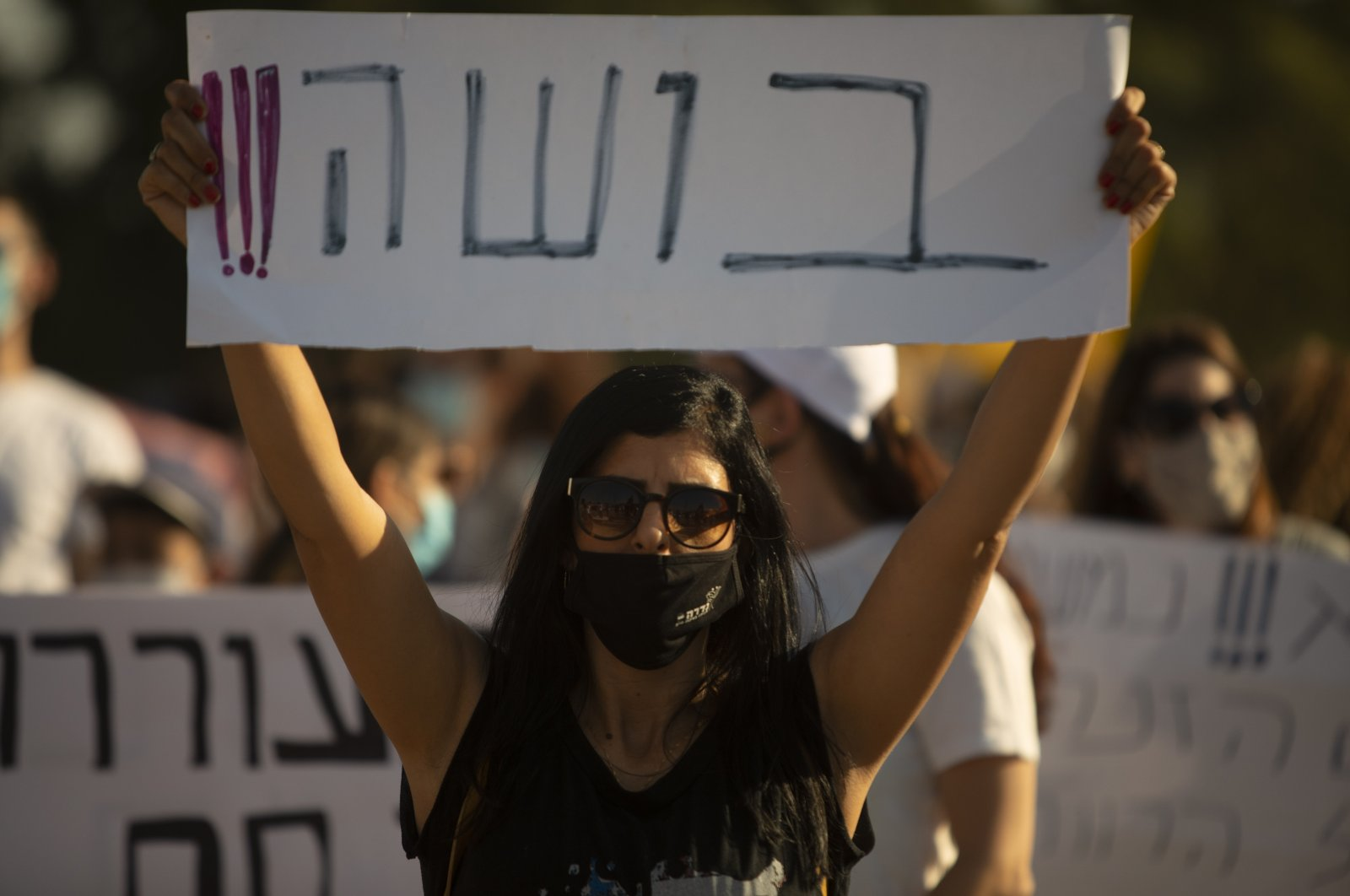 """An Israeli social worker holds a sign in Hebrew that reads, """"shame,"""" during a protest against the economic situation in the central Israeli town of Kfar Ahim, July 9, 2020. (AP Photo)"""