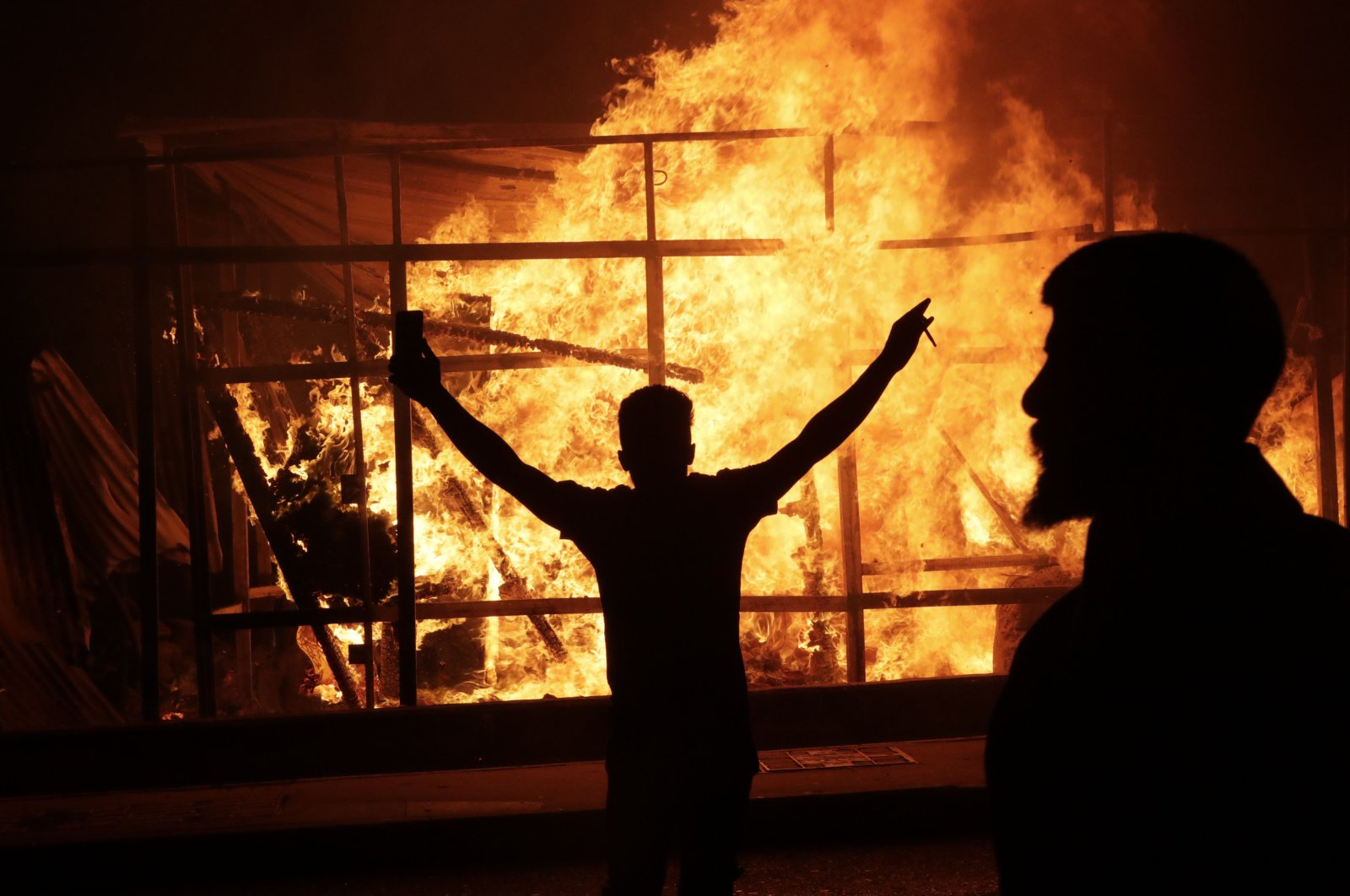 A Lebanese anti-government protester raises his arms in front of a burning wooden structure during a demonstration against dire economic conditions, Beirut, June 12, 2020. (AFP Photo)