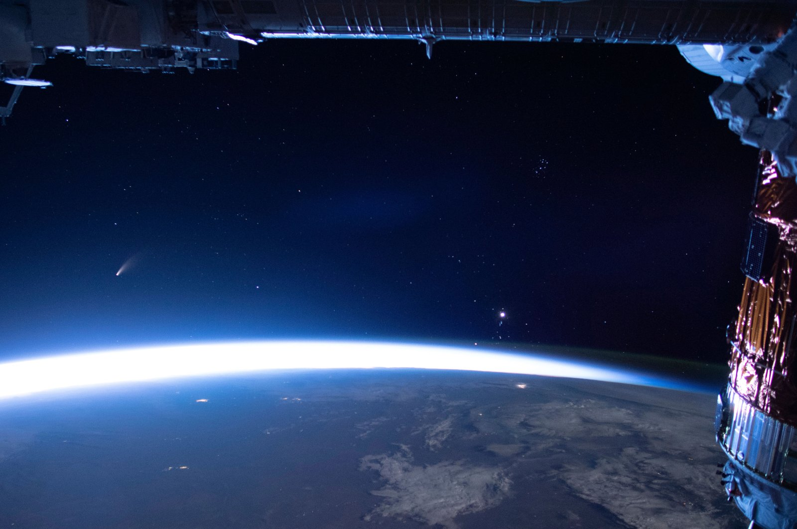 Comet Neowise (L) is seen in the eastern horizon above Earth in this image taken from the International Space Station, July 5, 2020. (NASA via AP)
