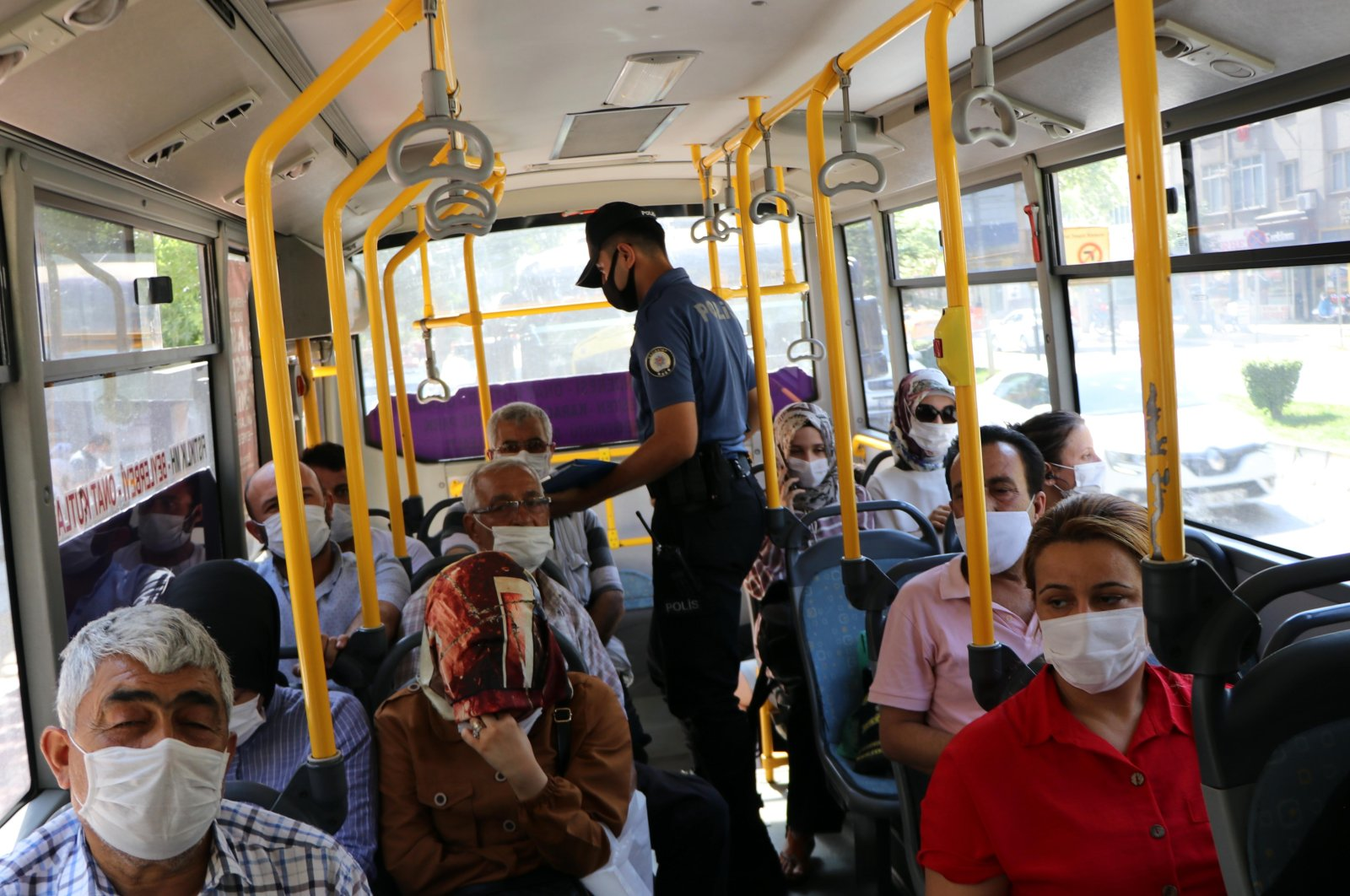 A police officer checks passengers in a bus as part of inspections against COVID-19 pandemic, in Gaziantep, Turkey, July 8, 2020. (DHA Photo)