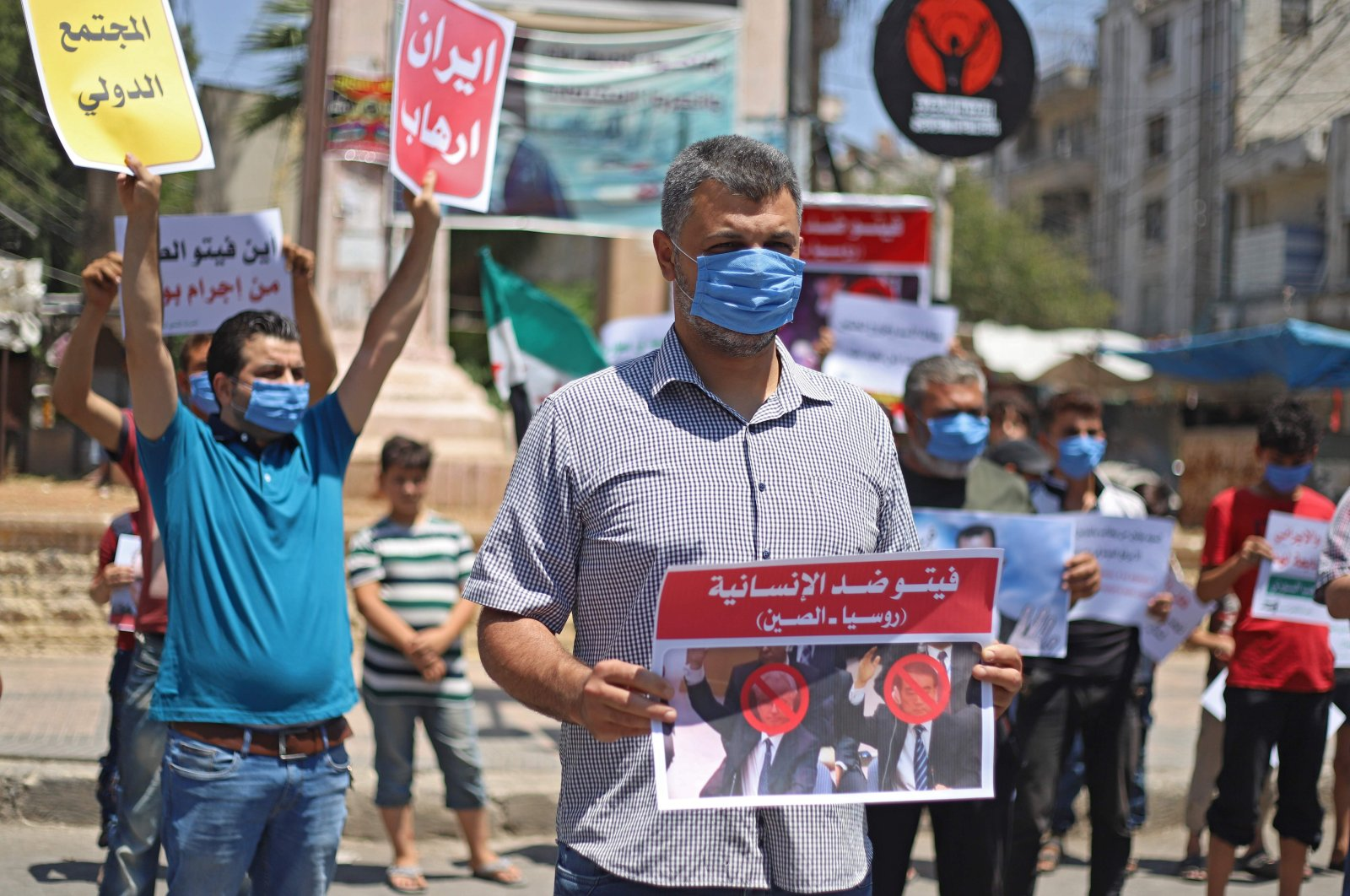 Syrian protesters carry placards expressing their opposition to Russia's attempt to reduce cross-border aid, in Idlib, Syria, July 10, 2020. (AFP Photo)