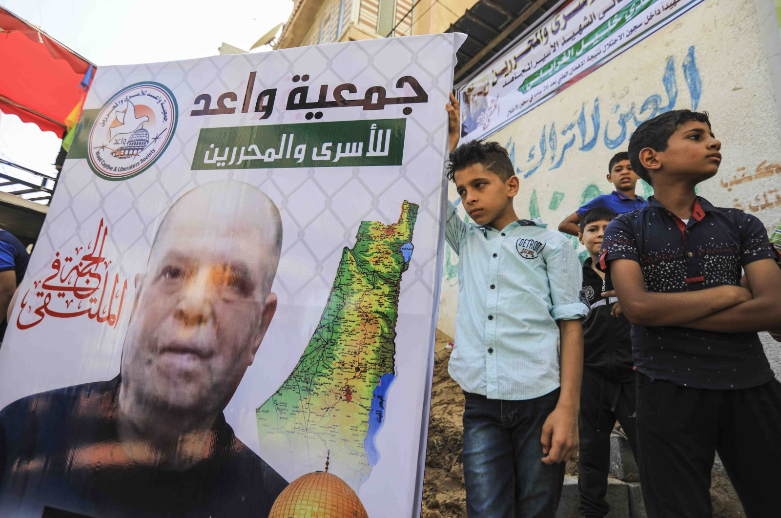 Youth stand next to a picture of Saadi al-Ghrabli (pictured), a Palestinian sentenced and imprisoned by Israel for life 26 years prior, outside a memorial service for him on the day of his death in Gaza City on July 8, 2020. (AFP Photo)